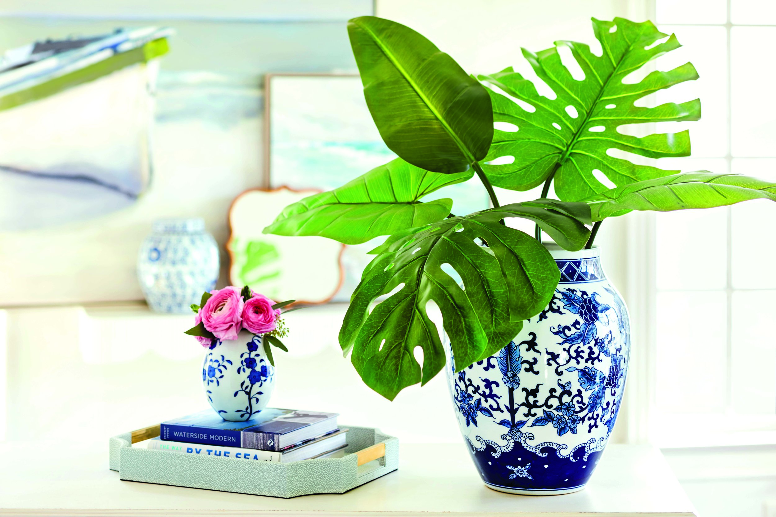 Tropical leaves in this simple arrangement with a few favorite accessories, set the tone for a less cluttered home without sacrificing your decor. Photo courtesy of Ballard Designs.