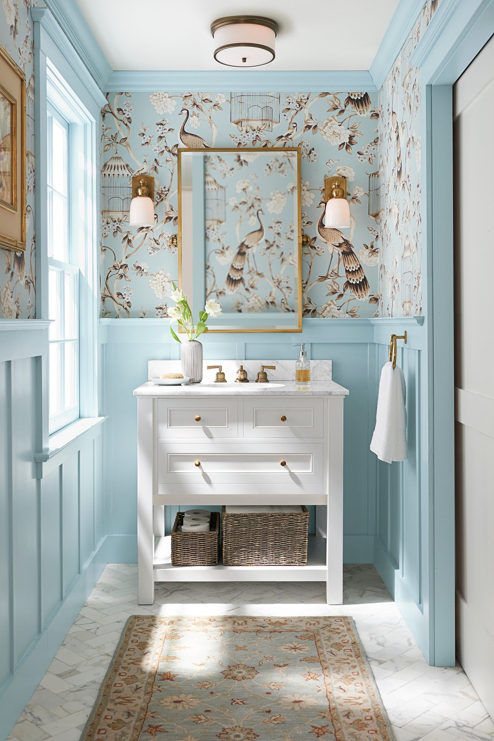 A serene spa-like powder room with classic white console, marble top, metal fixtures is set against a dramatic wall covering for a customized look.  Photo courtesy of Pottery Barn.