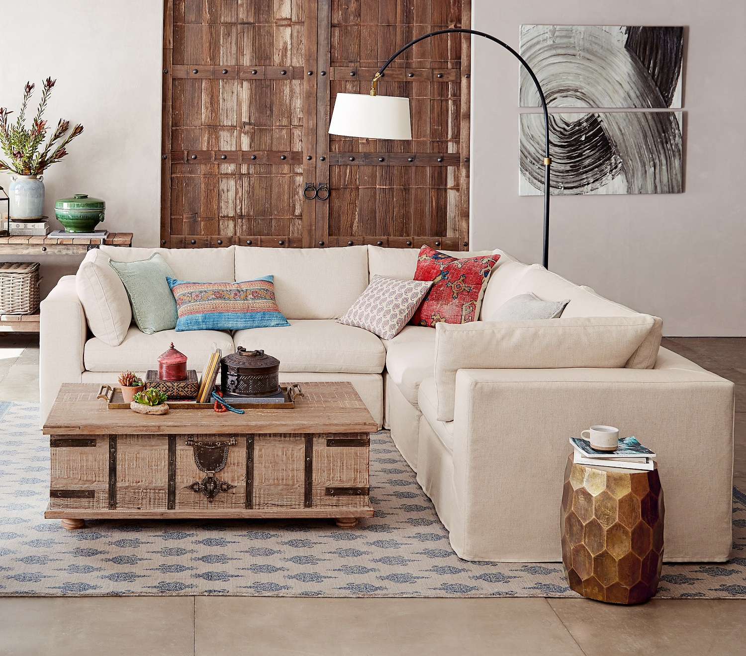 Establish a comfortable conversation area in an open floor plan with a this square arm, slipcovered corner sectional, a rug and large accent light to anchor the space. Photo courtesy of Pottery Barn.