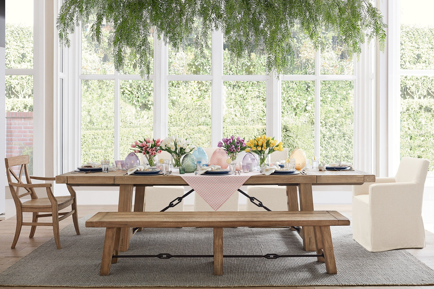 Layer a beautiful table with a few new touches for spring such as these bundles of tulips in glass vases and pastel blown glass eggs filled with strings of lights or votive candles. Shown: rustic, industrial-styled Benchwright dining table. Photo: Pottery Barn