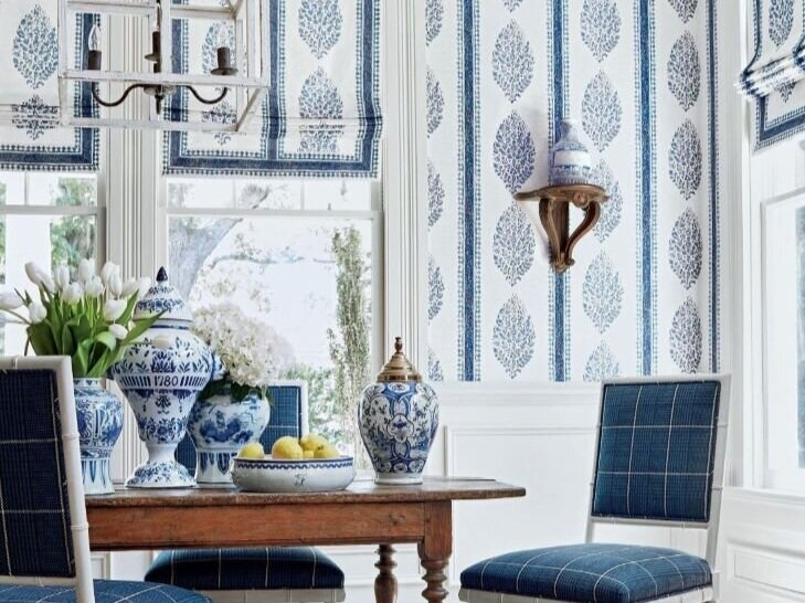 Pretty in blues. This dining room pairs Thibaut Design's Chappana wallpaper and printed fabric for roman shades. Darien dining chairs in Grassmarket check woven fabric in navy. Blue and white accessories. Photo: Thibaut Design