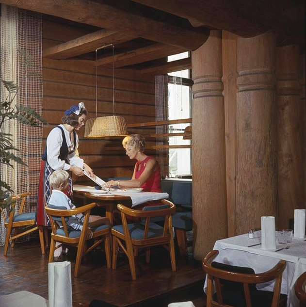 Color photograph from the Restaurant Kestikartano, early 1960s. Waiter wearing   Finnish traditional folk costume.  Ceiling lamp by Tynell with braided wicker shade and brass fittings. Image copyright by Museovirasto.