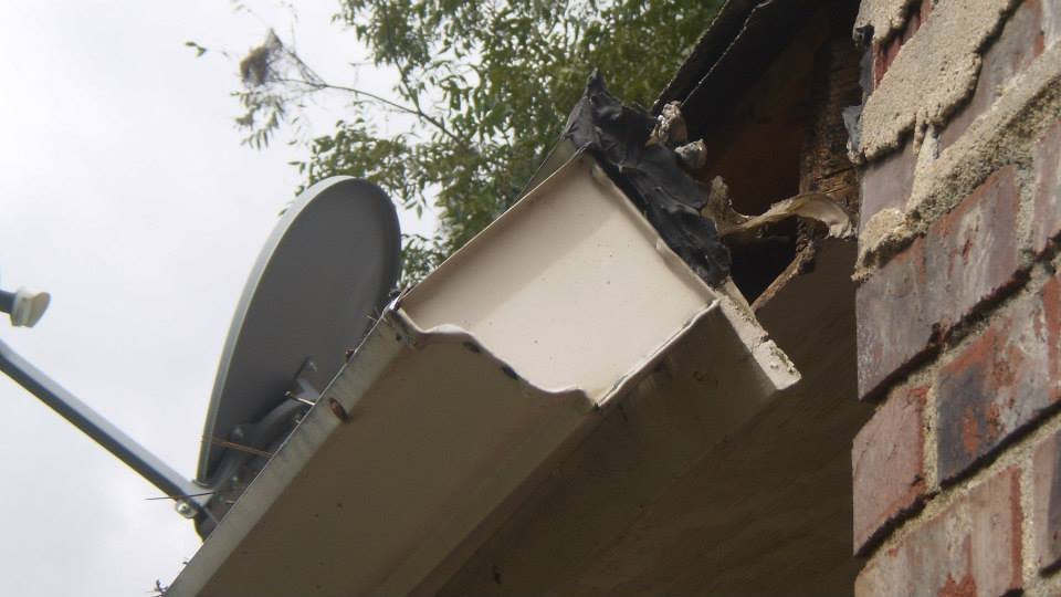 Fascia board is torn from soffit due to decay.