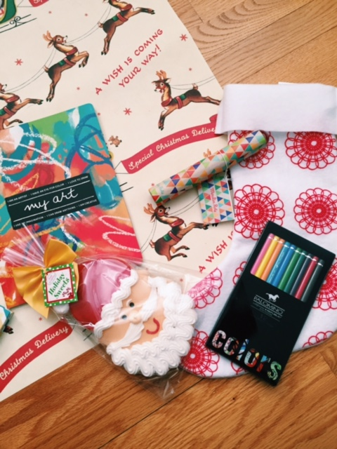 """From Left: """"My Art"""" prompted sketchbook, vanilla Santa sugar cookie (Christmas tree, Snowman, and Stocking available), a colorful kaleidoscope, colored pencil assorted set and snowflake stocking."""