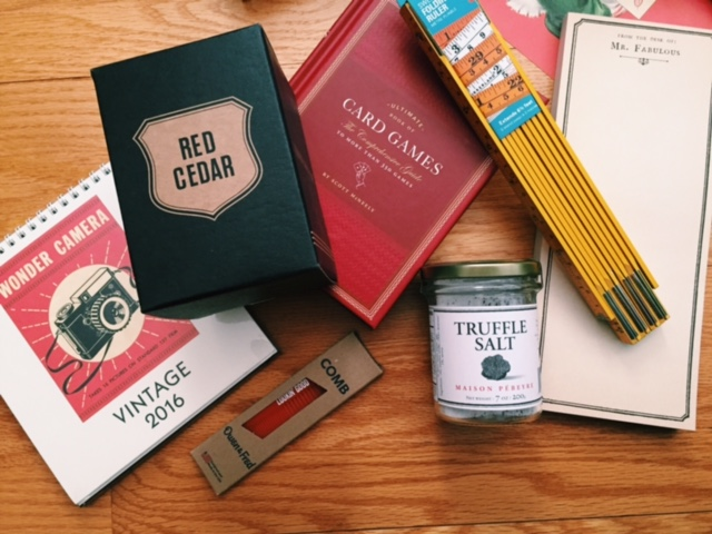 """From Left: a  vintage inspired  2016 desk calendar, a heartening red cedar candle, a red pocket comb, a handy book of card games, a carpenter's ruler like what his father used to use, truffle salt for the taste and the hilarious """"Mr. Fabulous"""" notepad."""