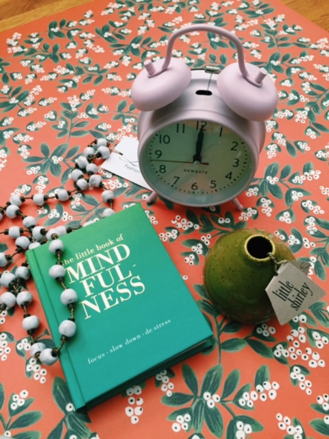 """From Top: The sweetest  wakeup  call- a flat pink alarm clock, """"Fashion with a purpose"""" handmade clay necklace, a purse-size mindfulness meditation book, and a Little Shirley bud vase (every purchase promotes cancer research funding)."""