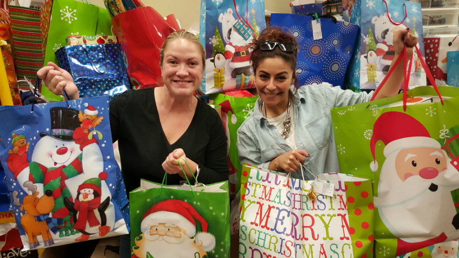 leigh and mouna packing bags for cumac's holiday wish list program
