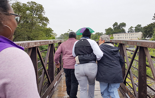 Rev. Pat Bruger walking with Teresa over a bridge at the Great Falls