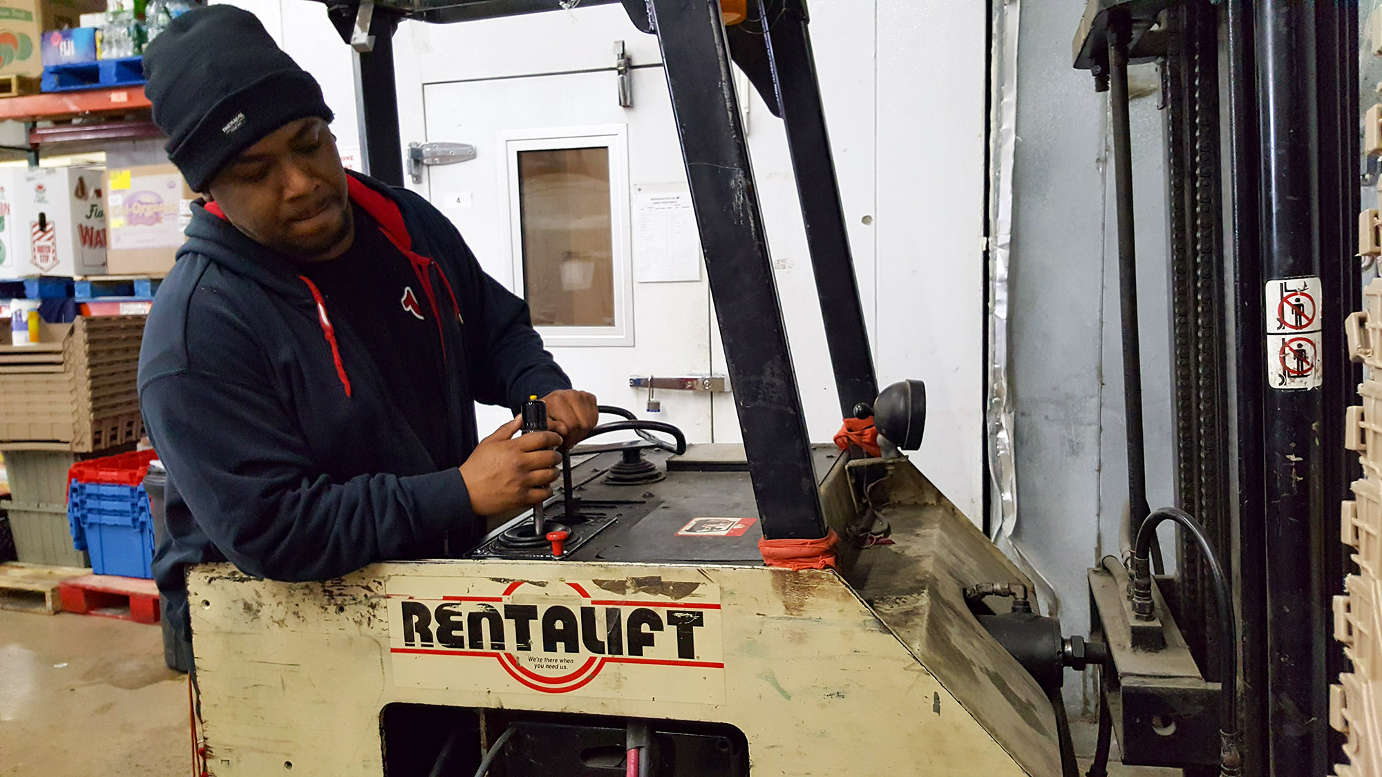 Anthony assisting in CUMAC's warehouse after his forklift training and certification