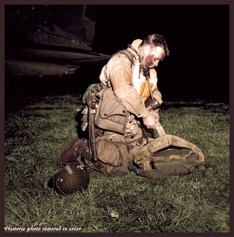 "Lt. Col. Robert Wolverton, C/O 3 Btn, 506 Parachute Infantry Regiment, 101st Airborne Division, checking his gear before boarding the C-47 ""Dakota"", 8Y-S, ""Stoy Hora"" of the 440th Troop Carrier Squadron at an airfield in Exeter, England.   The evening of the 5th of June 1944.    On that evening in June 1944, he gathered his men in an orchard adjacent to what is now Exeter airport, and said:    ""Men, I am not a religious man and I don't know your feelings in this matter, but I am going to ask you to pray with me for the success of the mission before us. And while we pray, let us get on our knees and not look down but up with faces raised to the sky so that we can see God and ask his blessing in what we are about to do.      ""God almighty, in a few short hours we will be in battle with the enemy. We do not join battle afraid. We do not ask favors or indulgence but ask that, if You will, use us as Your instrument for the right and an aid in returning peace to the world.  ""We do not know or seek what our fate will be. We ask only this, that if die we must, that we die as men would die, without complaining, without pleading and safe in the feeling that we have done our best for what we believed was right.  ""Oh Lord, protect our loved ones and be near us in the fire ahead and with us now as we pray to you.""  Sadly, within hours, the orator himself was dead; a cruel twist of fate meant his feet never touched French soil.  Lt Col Robert L Wolverton (aged 30), was killed by ground fire and left suspended by his parachute from an apple tree in an orchard just north of the hamlet of St Côme du Mont in Normandy.  (Nb. of the 15 men in his 'stick', 5 were KIA on D/Day, 8 taken as POWs and 2 unaccounted for)   (Colourised by Johhny Sirlande from Belgium)"