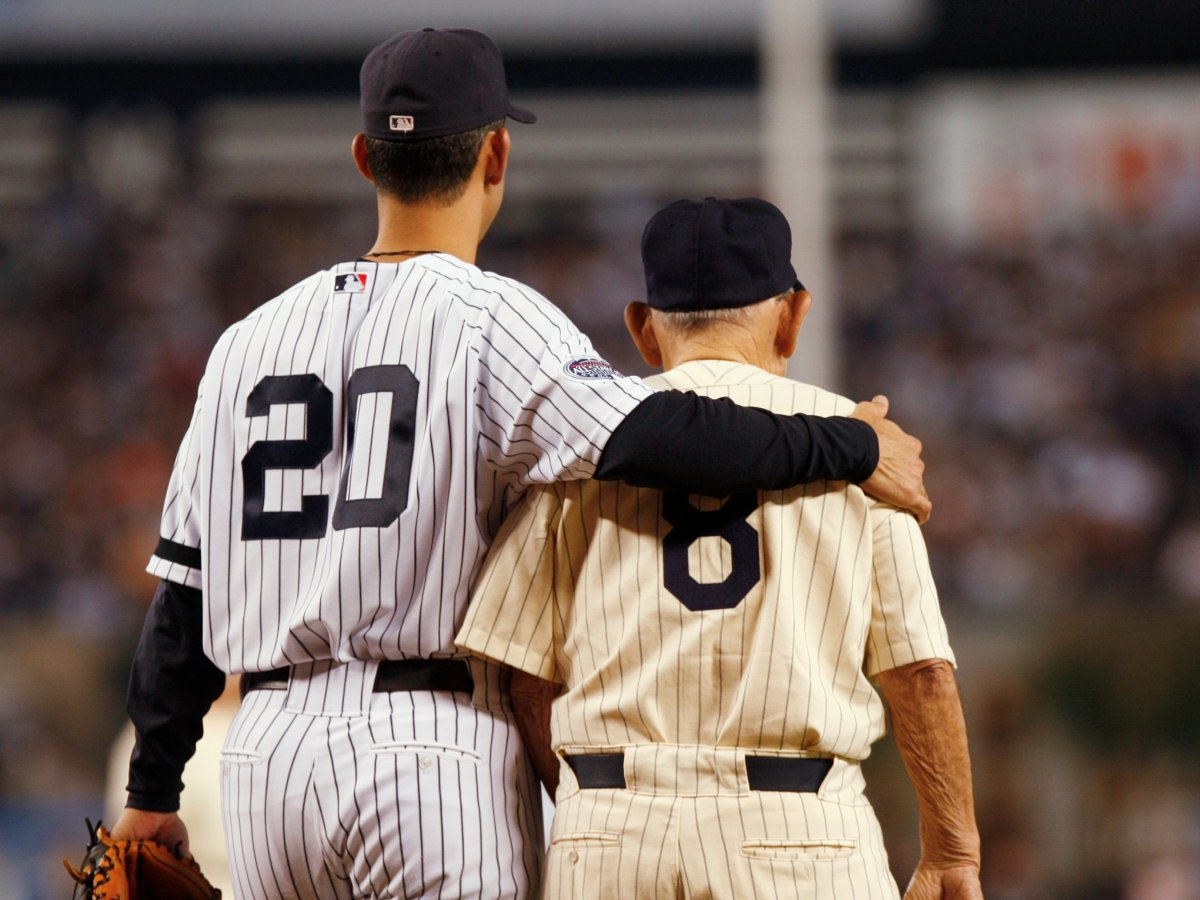 I love this picture. Jorge Posada with his arm around Yogi Berra. Even without the numbers, both famous Yankee catchers are unmistakable.