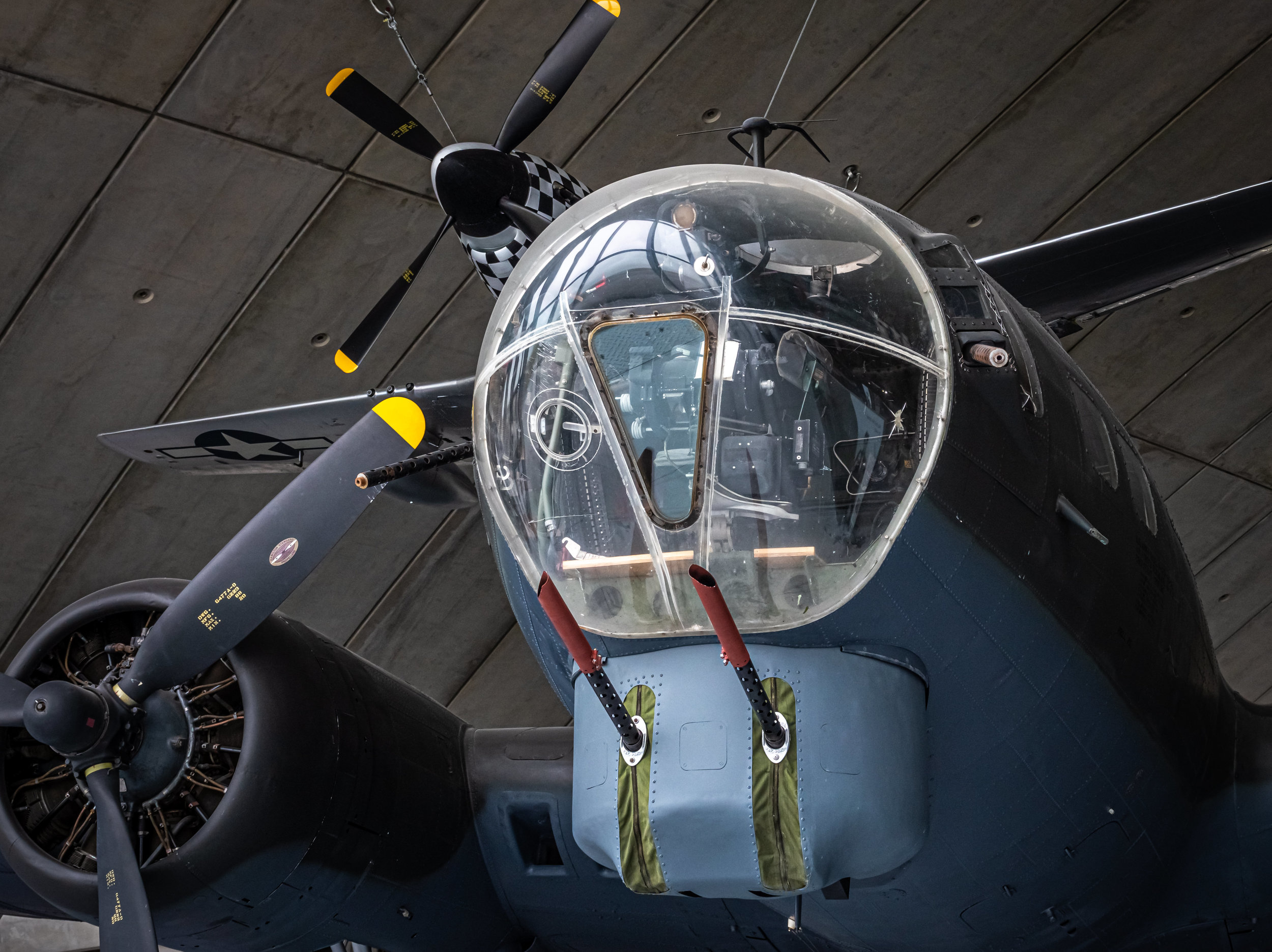 The nose of this B-17 Flying Fortress shows the bombardier's station, twin .50 caliber chin guns and the two side .50's that the bombardier manned when he was not at his Norden bomb sight. Appropriately hanging from the ceiling overhead is a P-51 Mustang, the great long-range fighter that so often protected the B-17s.