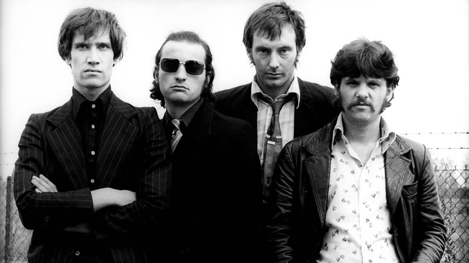 """In their mid-70s prime, Dr. Feelgood stood as arguably the most vital of the so-called """"pub rock"""" acts to emerge. They were a grungy, cutting, sneering antidote to the polished, formulaic glam rock or treacly bubblegum pop dominating the charts at the time in the UK. Though bands like them harkened back to the devotedly pure R&B, blues, rockabilly and soul of the mid-60s British music scene, their uncompromising sound and attitude did actually pave the way for numerous punk and new wave bands who by decade's end were stealing the show (by then Dr. Feelgood was struggling to stay relevant , though doing so better than many of the glam bands they stood in defiance of)."""