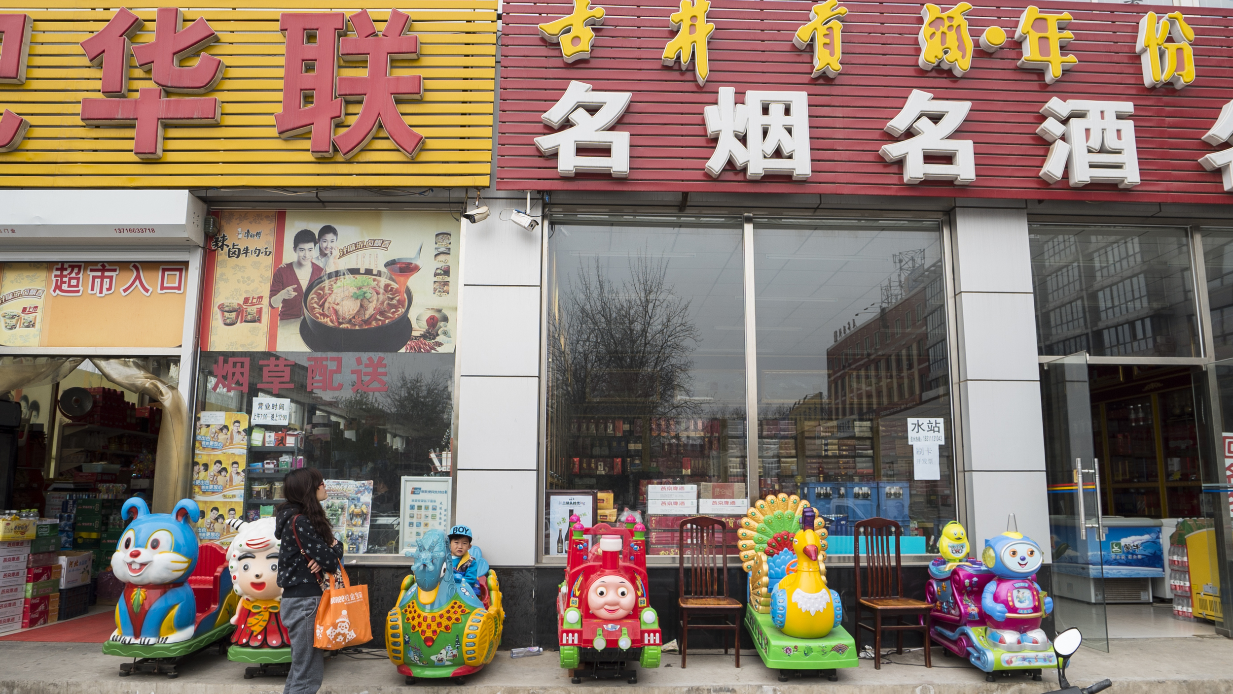 A young boy cautiously rides a knockoff cartoon character outside a supermarket in Changping district, Beijing. Photo: Abel Blanco.