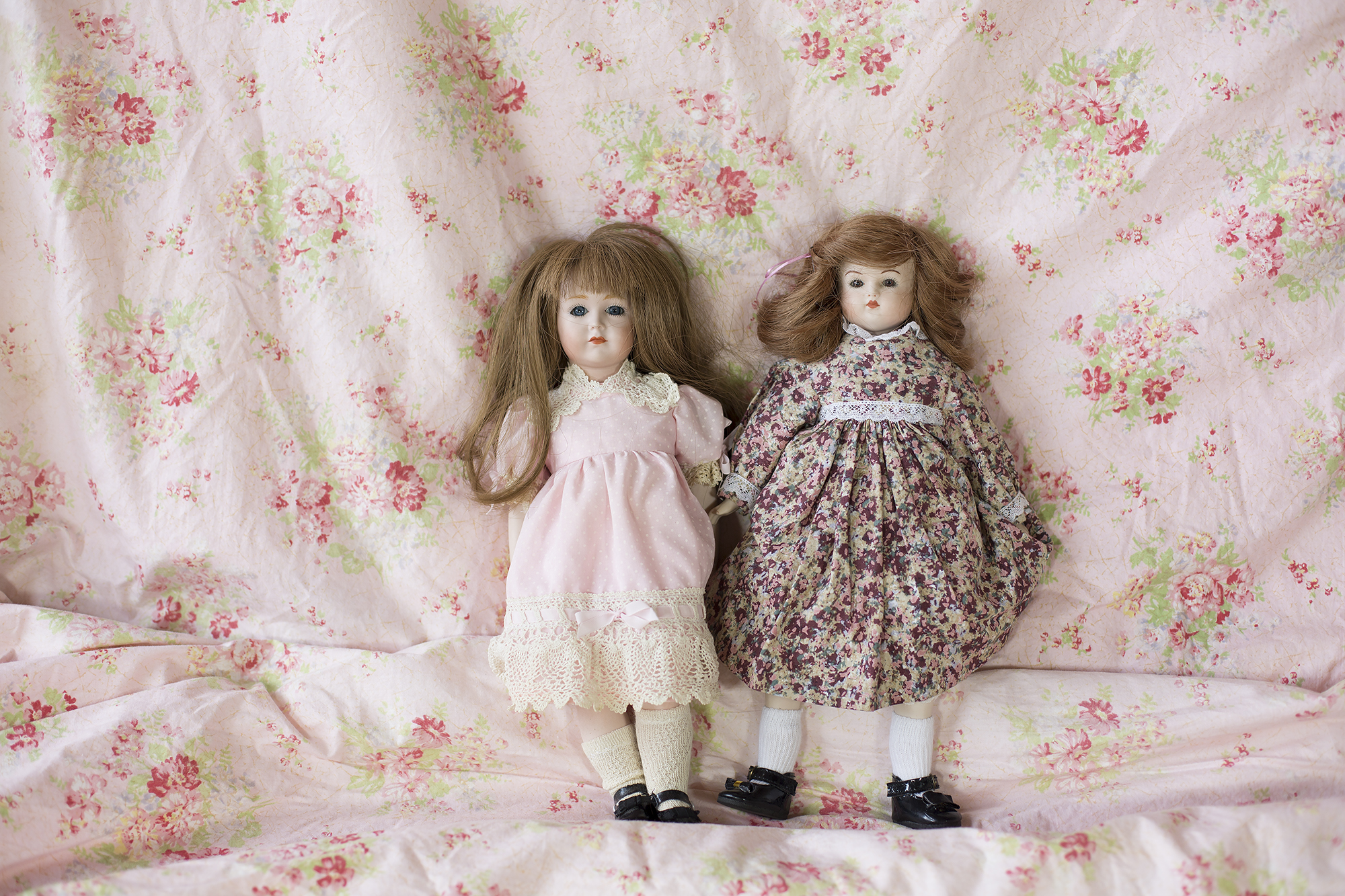 Reproduction dolls. The doll on left a Simon and Halbig with K R (stands for Kammer and Reinhardt) which took over S&H in 1920 and was given to Judith by her mother in law. She is lovingly dressed in pink and has a sweet face. The doll on right in floral was made in 1986.