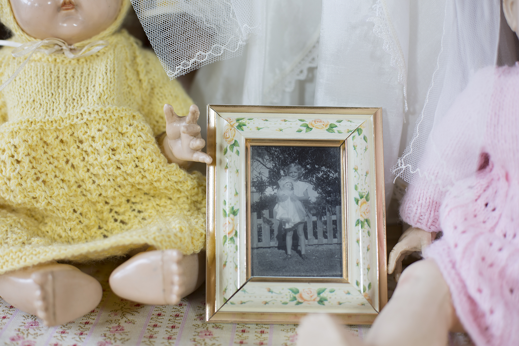 """A photograph of a young Judith with her """"Walkie Talkie"""" doll wearing her bride outfit, taken at the Selwyn Huts in the 1960s."""
