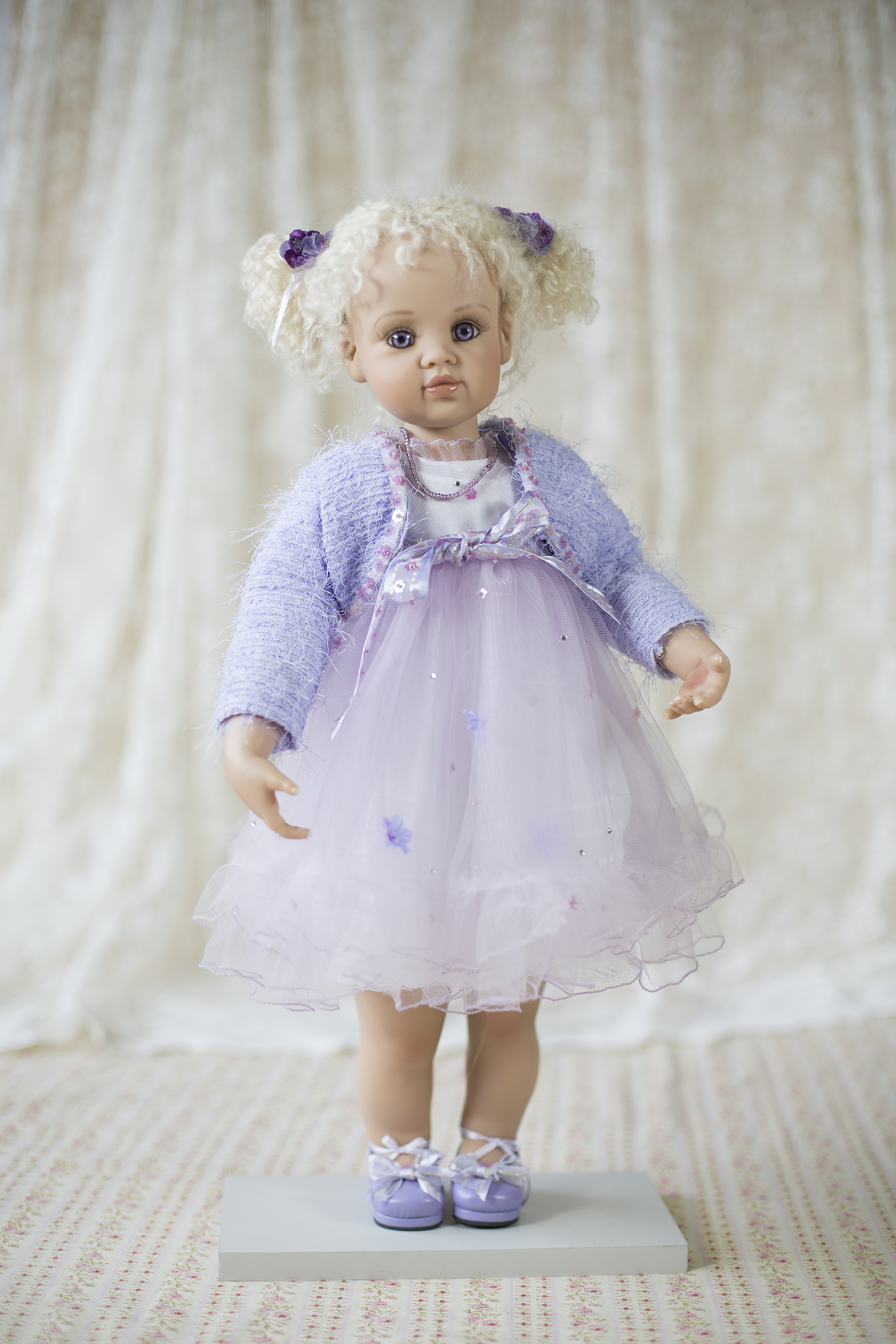 """Tiffany by  Jan McLean  2002. Limited edition 34 standing 22"""" tall. She is a vinyl collectors doll with on 3500 worldwide. """"Tiffany brings out the parent in me"""" says Judith who loves her soft lavender dress with layers of sequinned and flower trimmed tulle wearing delightful lavender shoes. Her little fluffy sweater is also trimmed with sequins and she has velvet flower's in her blonde mohair curls with a cute little innocent face.She has a lovely crystal necklace with gorgeous piercing violet eyes, you just cant take your eyes off her."""