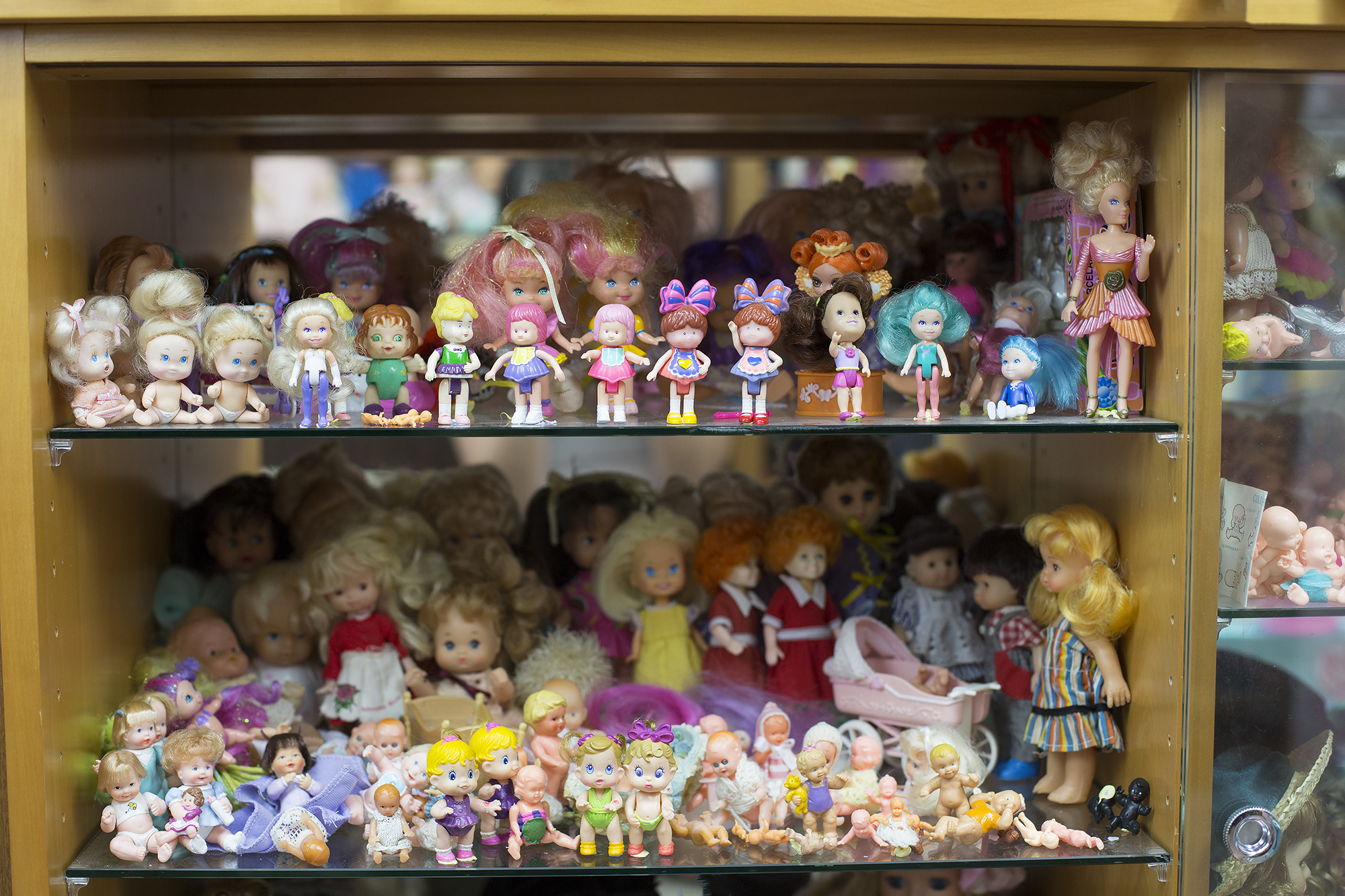An assortment of little dolls. You can see at the bottom the two with curly red hair are Annie dolls.