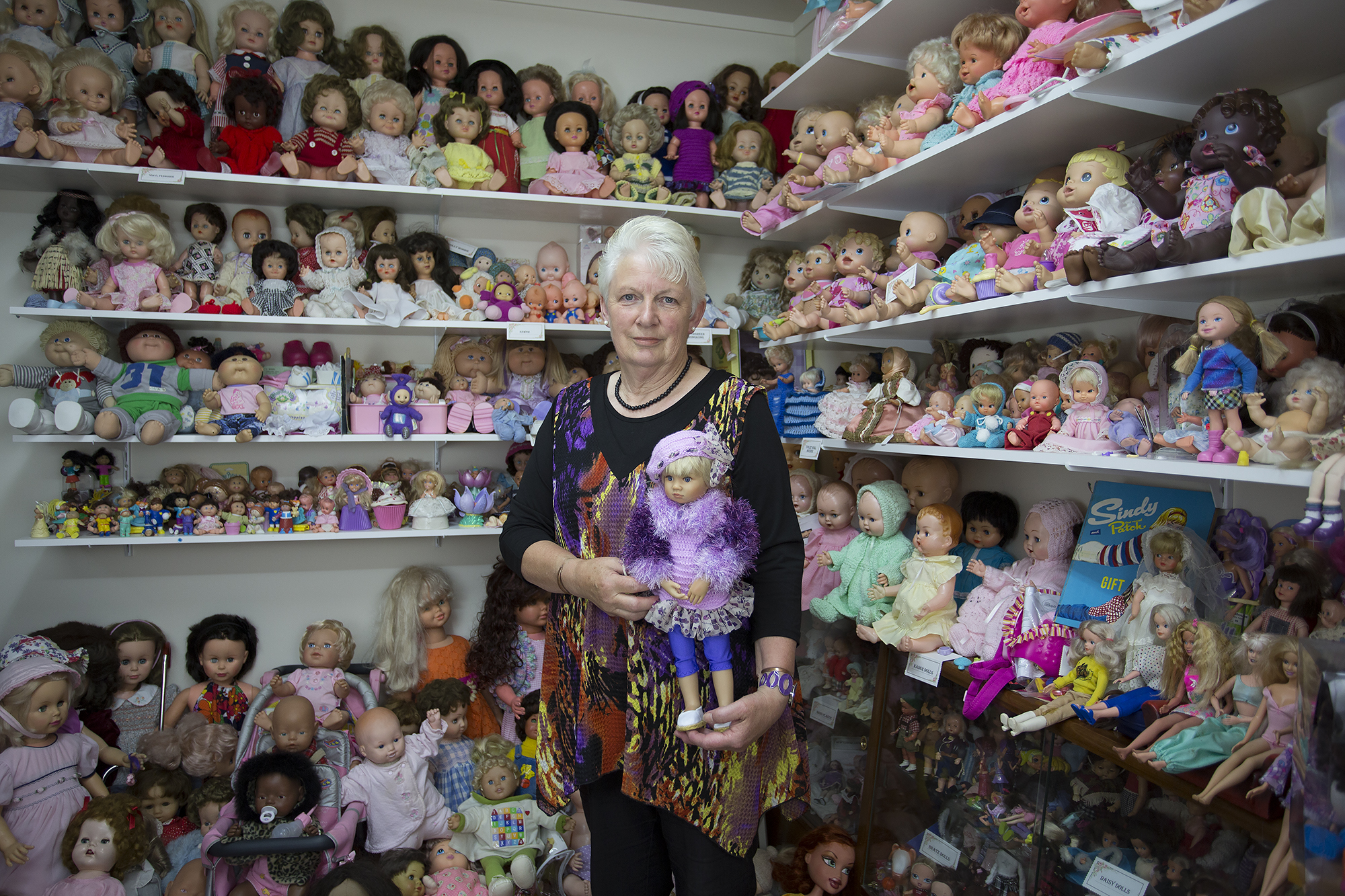 Judith amongst her collection over over 2000 dolls, holding a Kidz n Cats doll.