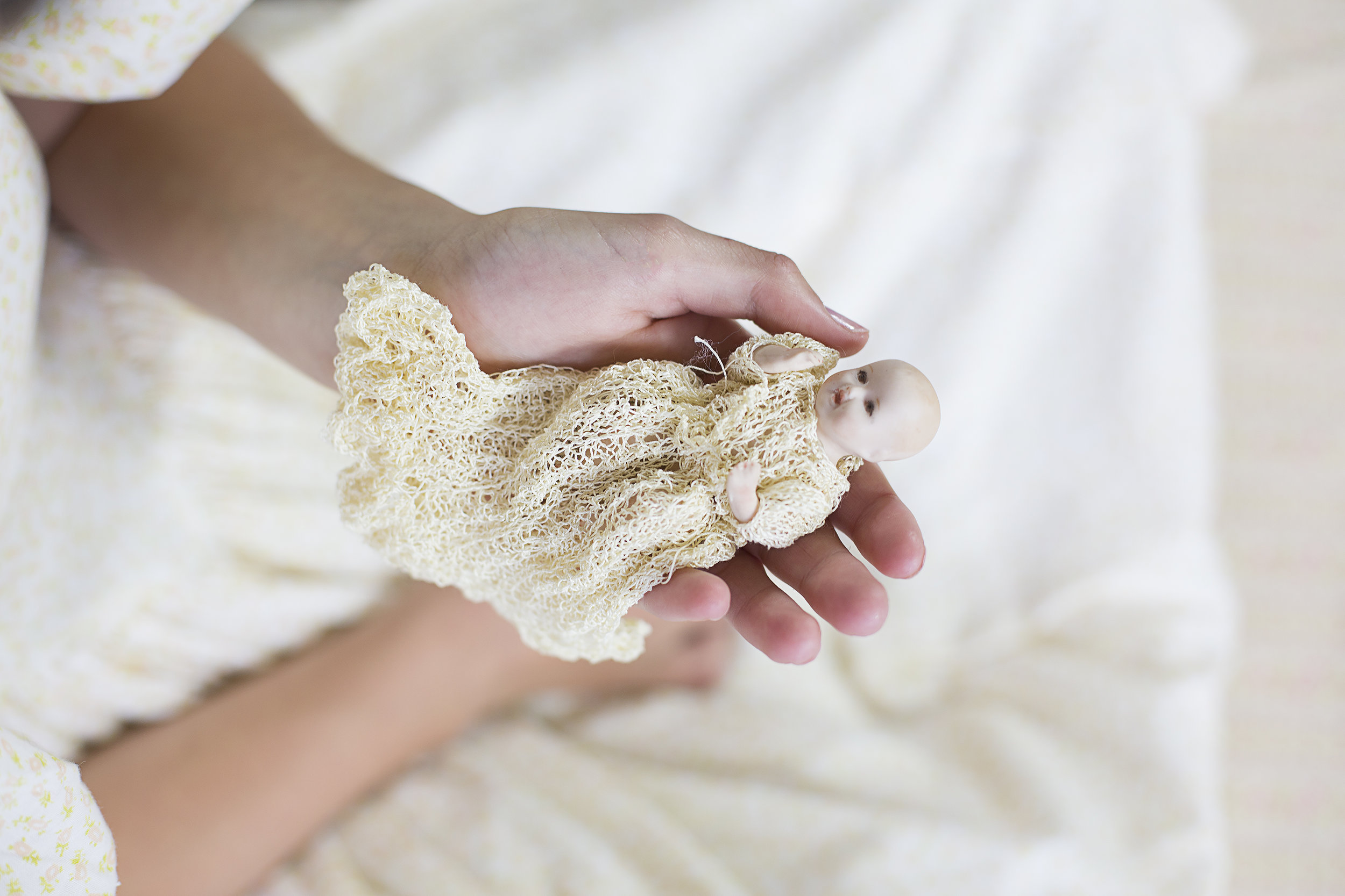 """This little porcelain doll measuring 3.5"""" wearing a fine crocheted christening gown was purchased at the Brisbane doll show W  inter W  onderland in 1999. The very fine outfit was given to Judith a year ago, it fits the previously naked doll perfectly."""