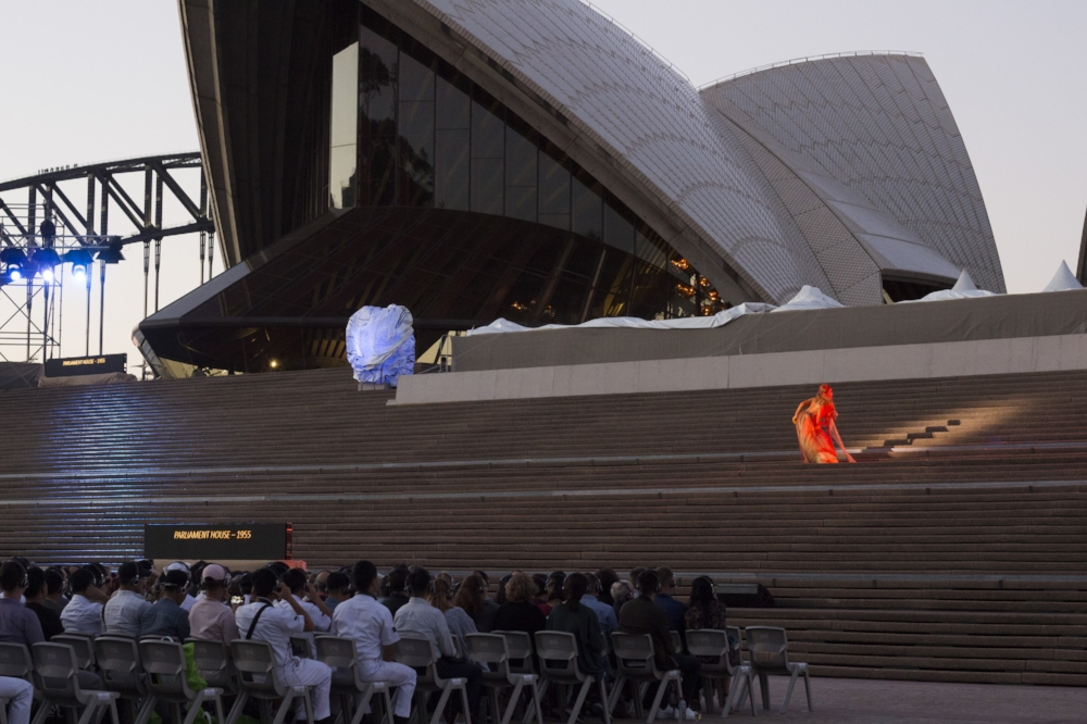A performer on the Opera House steps at dusk makes for an ethereal sight.