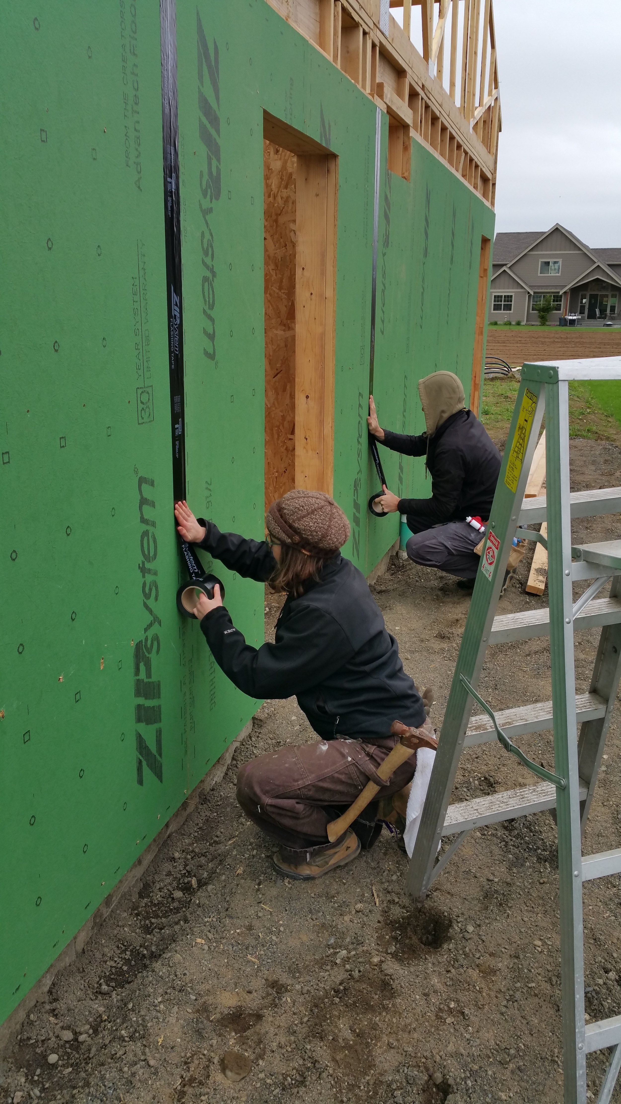 Our Technicians Brenda (L) and Stephen (R) applying Zip System flashing tape to seams.
