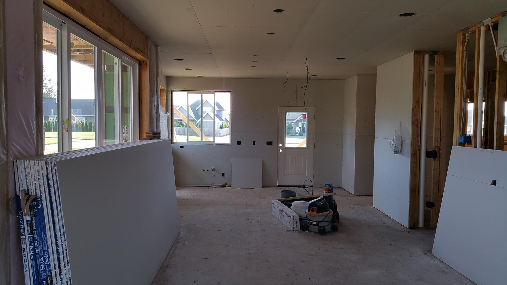 Standing in the living room, looking towards the dining room and kitchen.  With interior walls close to being done, interior trim work, flooring and cabinets will be installed.