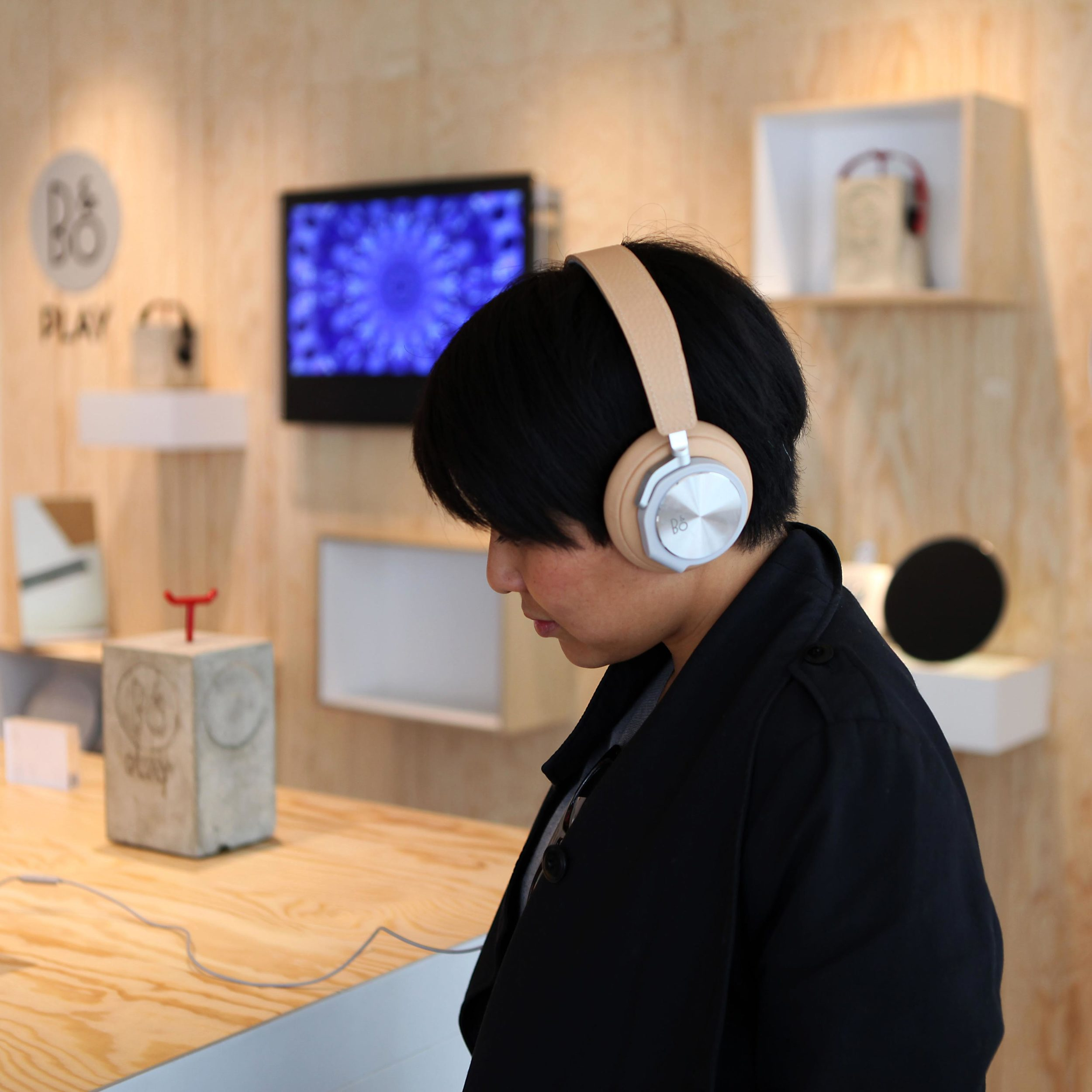 Man listening to a B&O PLAY product in a store constructed according to the shop-in-shop concept by Johannes Torpe Studios