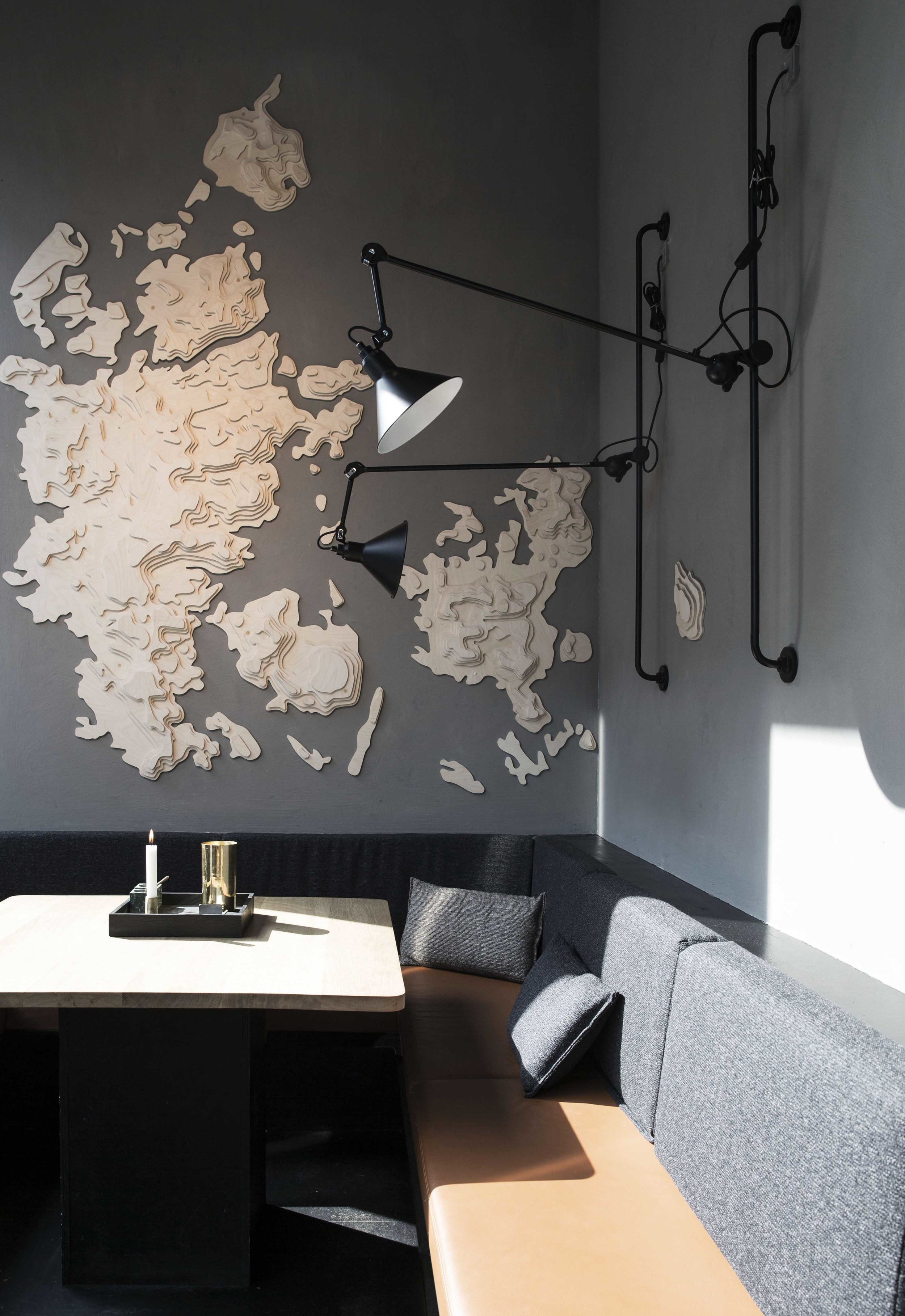 Seating corner with bespoke furniture at Palæo restaurant with map of Denmark mounted to the wall