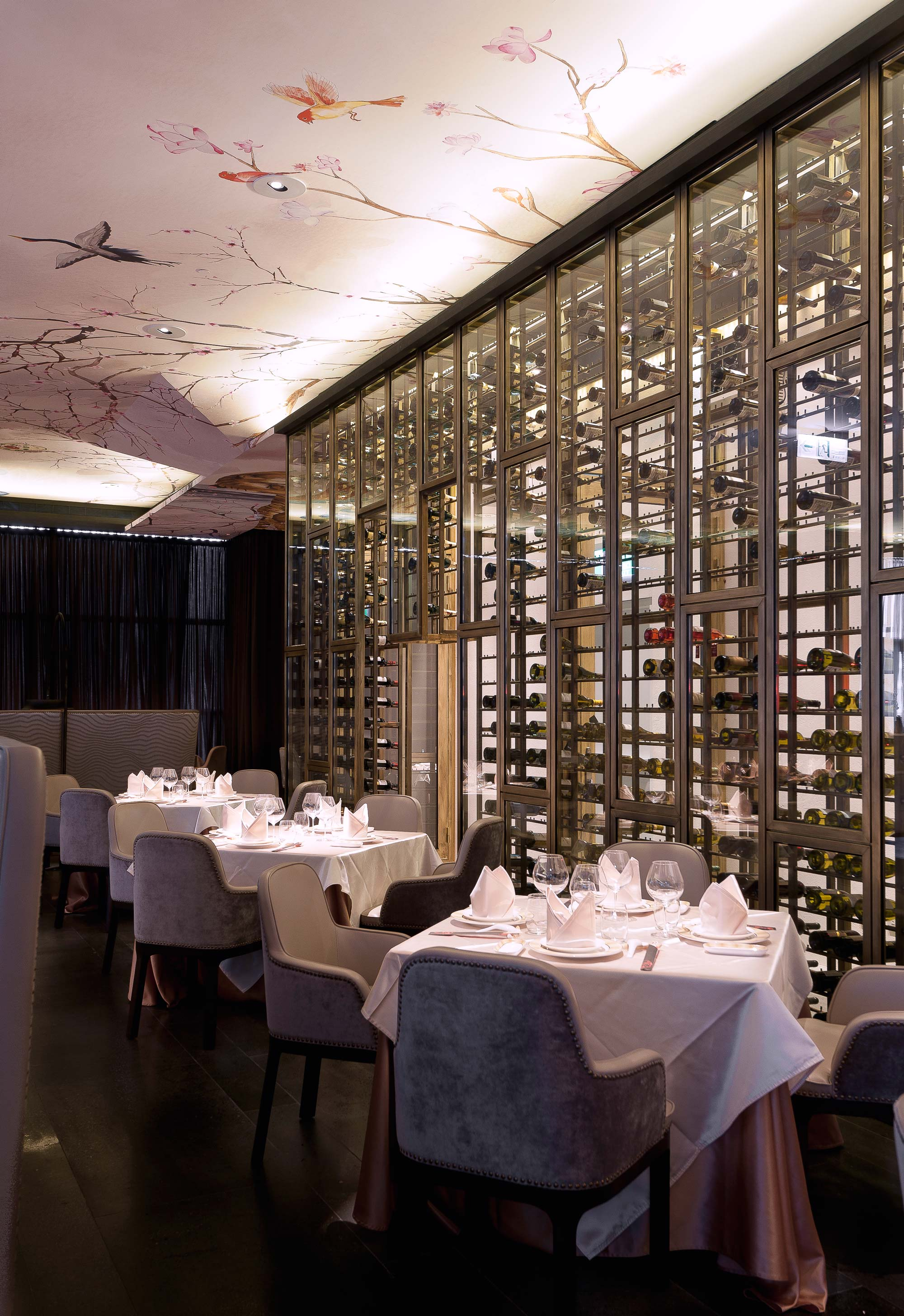 Restaurant interior featuring a wall-sized wine case, bespoke tables and chairs crowned with a China-inspired hand-painted artwork on the ceiling