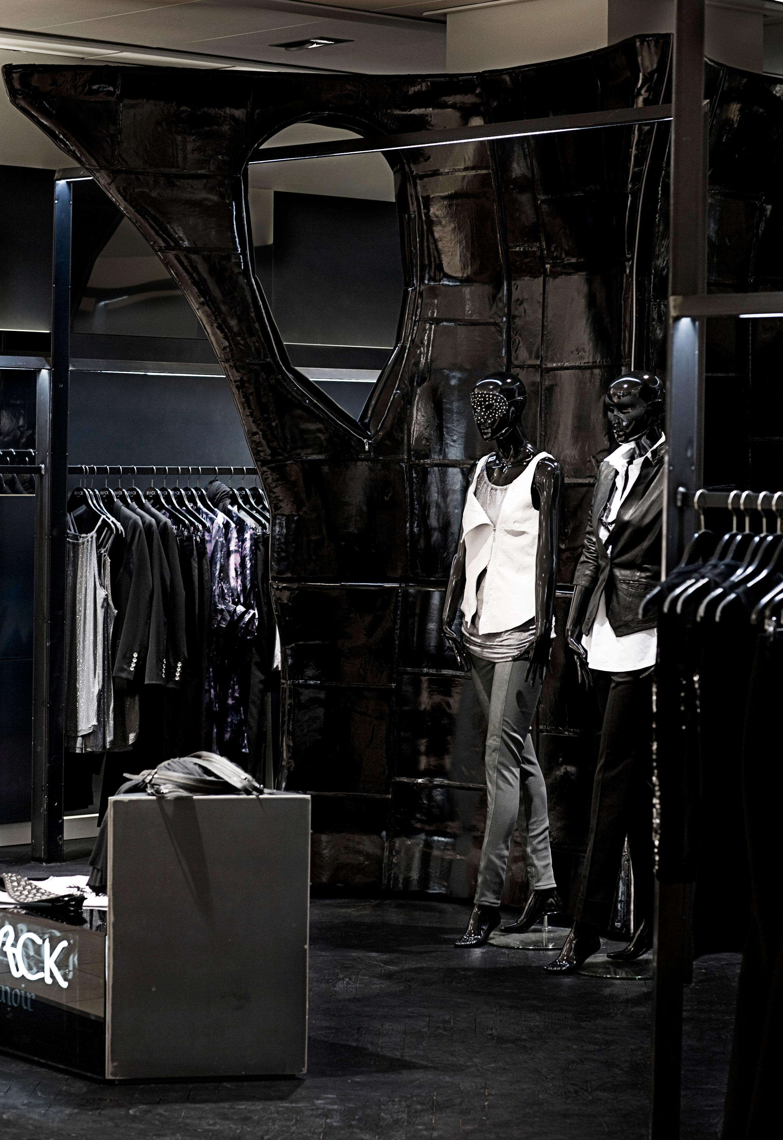 Interior design of Bllack Noir by Johannes Torpe Studios featuring a black organically shaped sculpture and two mannequin figures