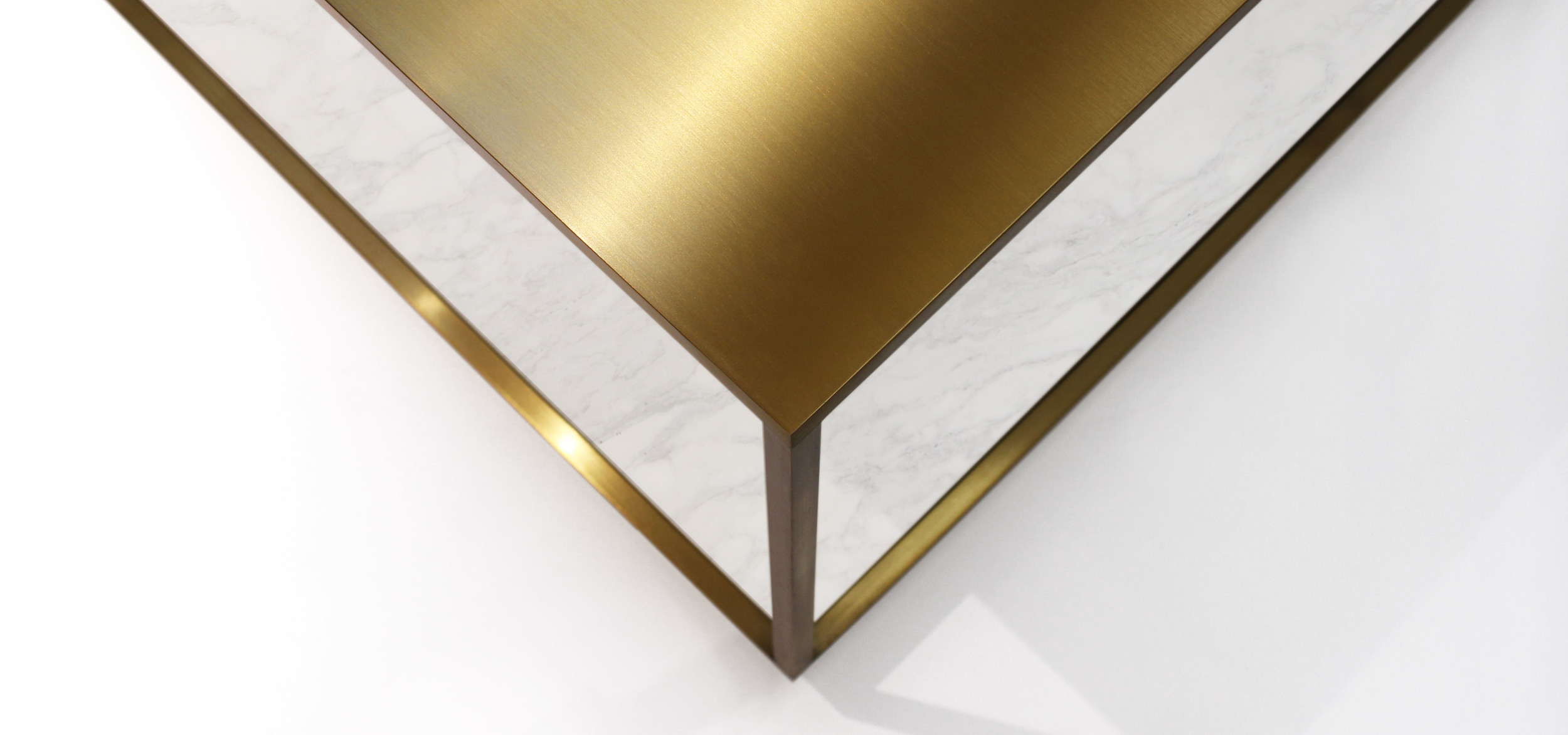Top view on corner of a table made of marble and brass as a part of a furniture collectiondesigned for Bang & Olufsen's global stores