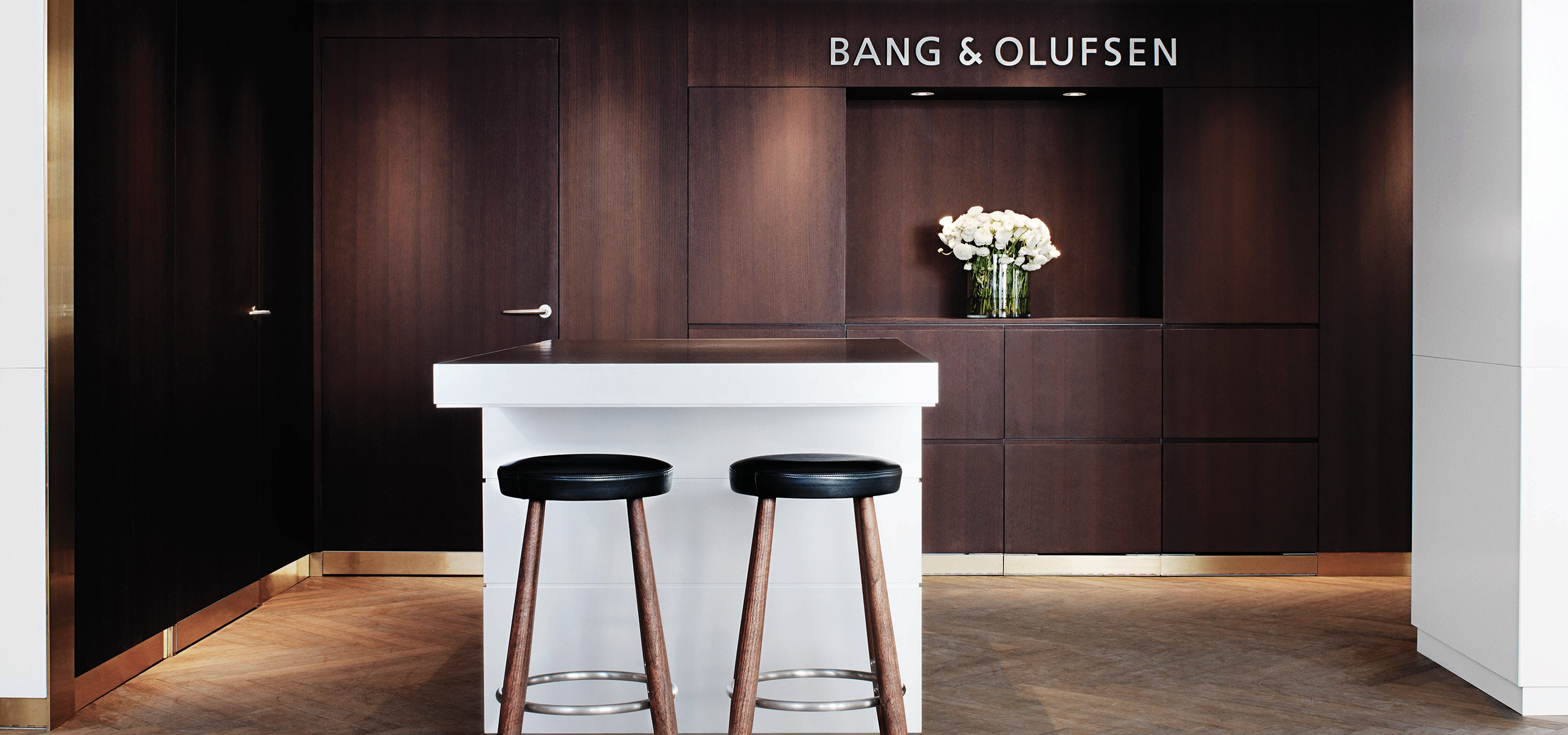Two bar stools standing in front of white counter at Bang & Olufsen store in Copenhagen