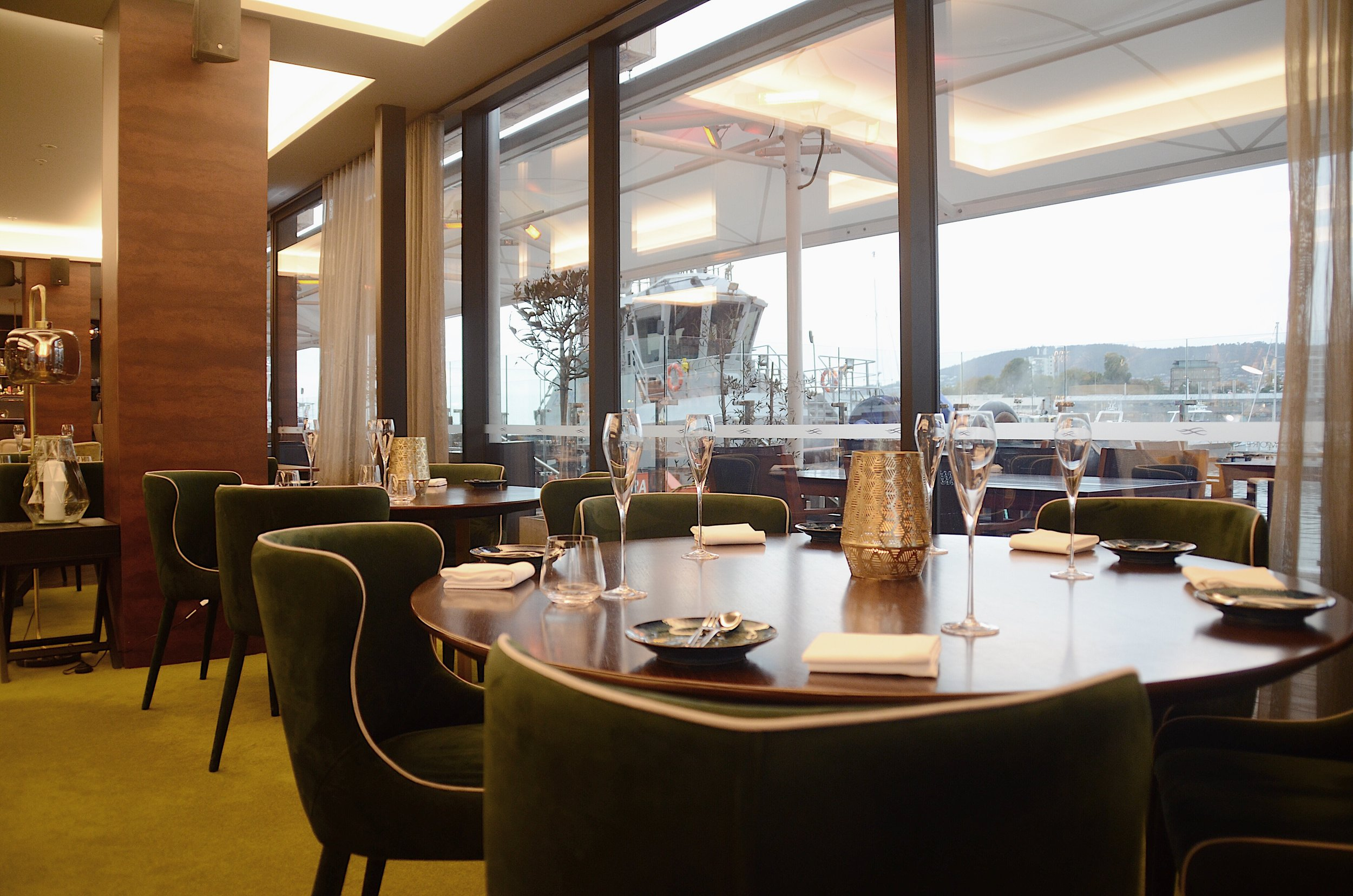 Big windows and green velvet chairs at The Lounge by Frogmore Creek