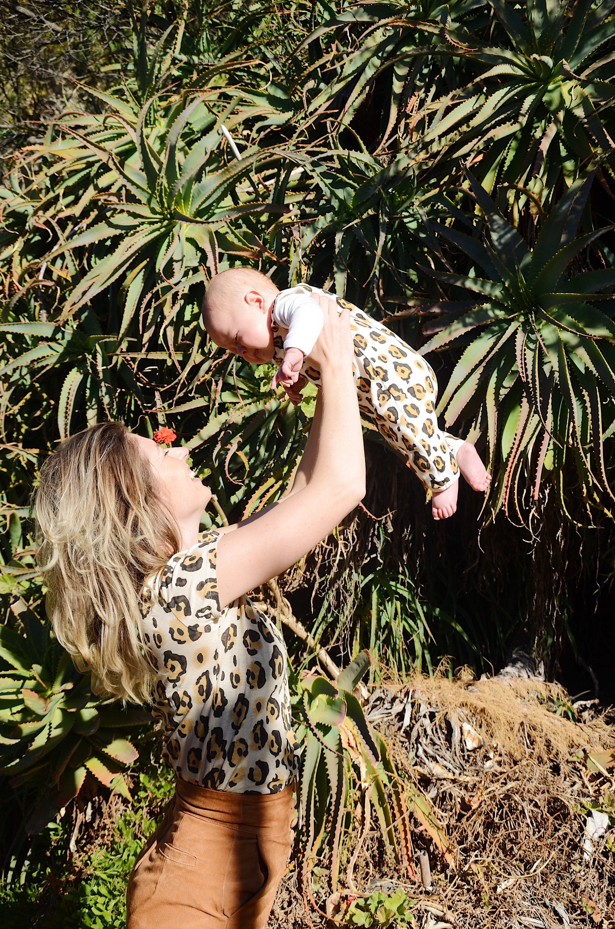 lifting Teddy above my head in front of cactus in matching leopard print