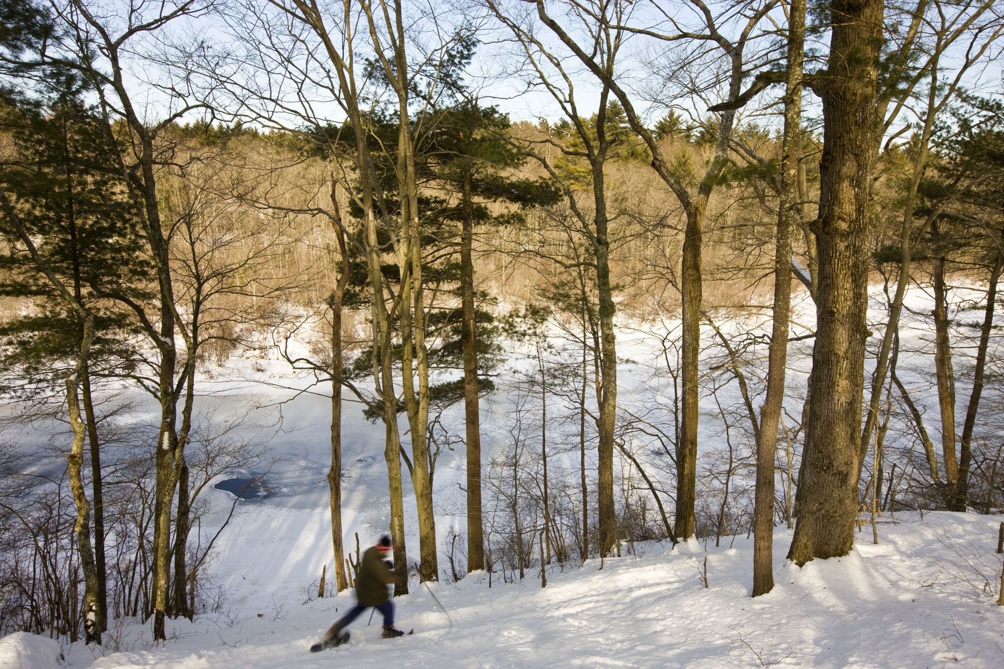 A man snowshoes next to the Indan Head River at the Tucker Preserve in Pembroke, Massachusetts.  Wildlands Trust of Southeastern Massachusetts.