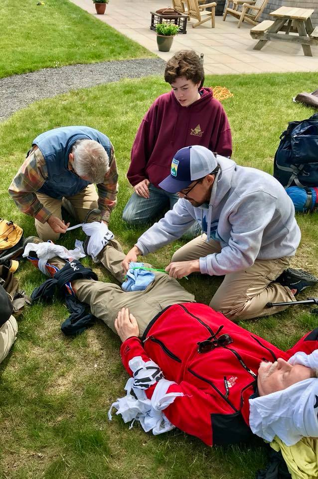 Wildlands staff and volunteers work through a staged medical emergency scenario during the wilderness first aid class.