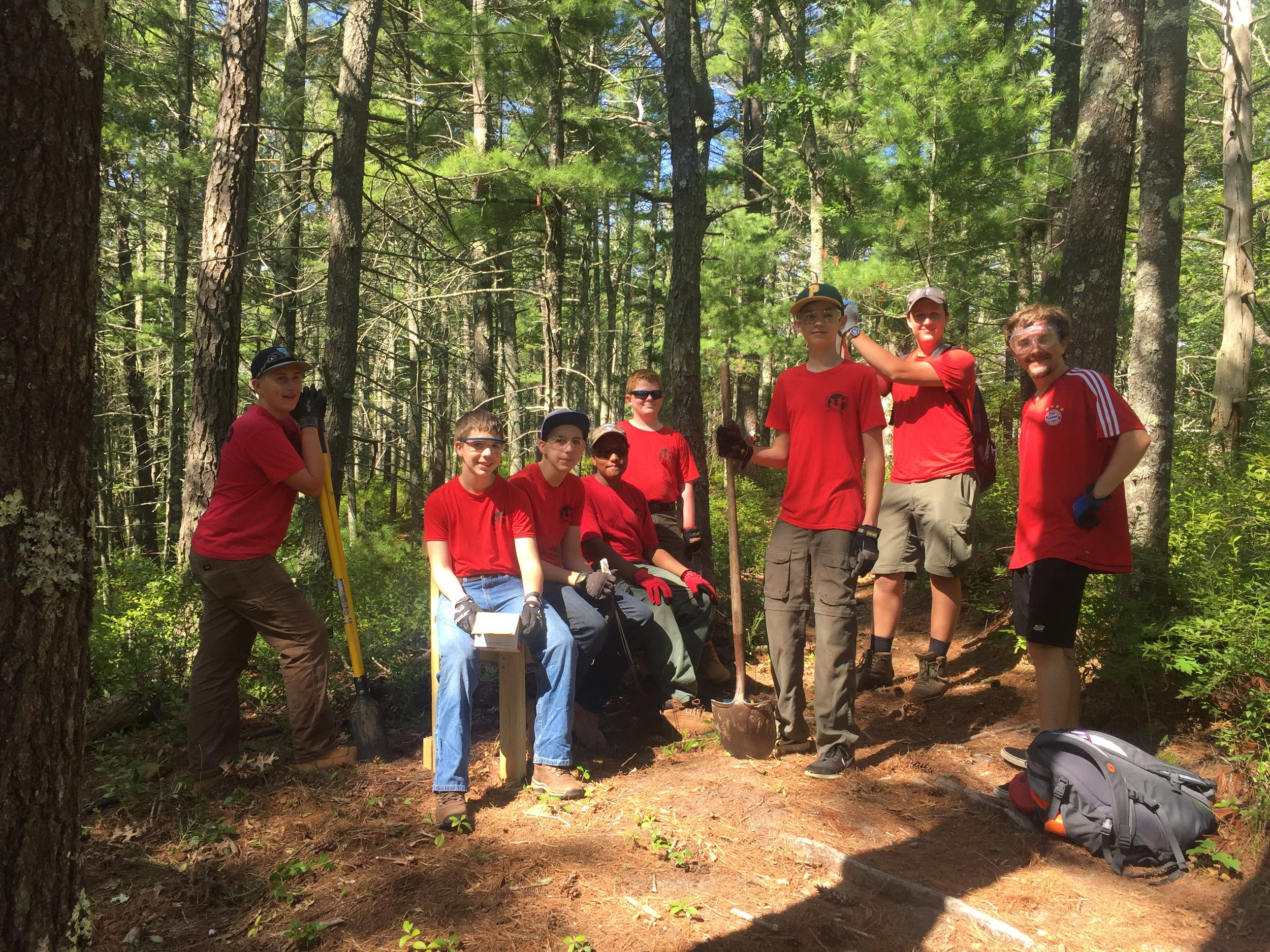 John Schelling, second from right, and the rest of Troop 1620 install one of four recently built benches.