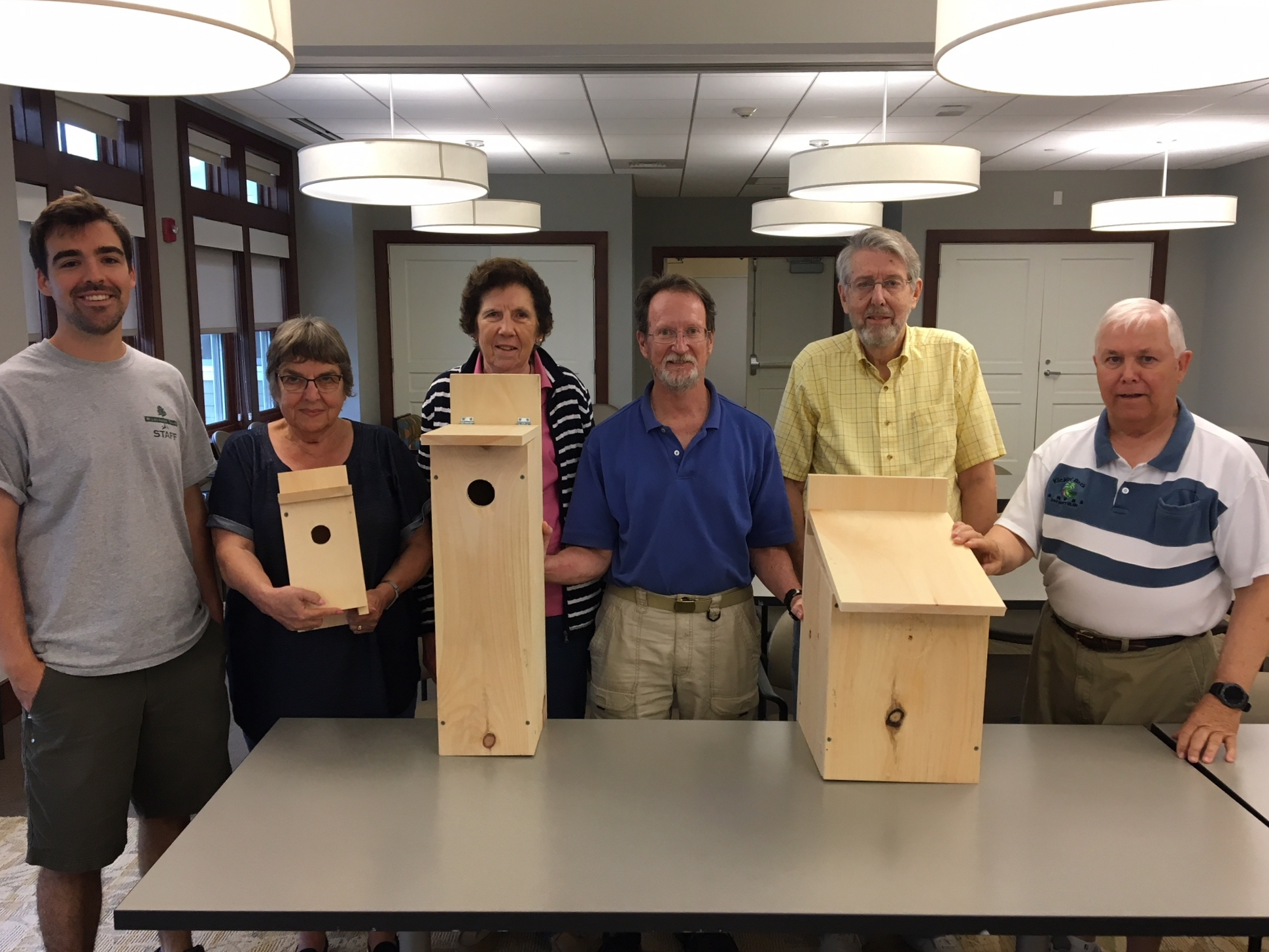 Conor Michaud (far left) and the residents of Fairing Way show off three of the bird boxes they built: (from left to right) a bluebird box, a norther flicker box and an eastern screech owl box.