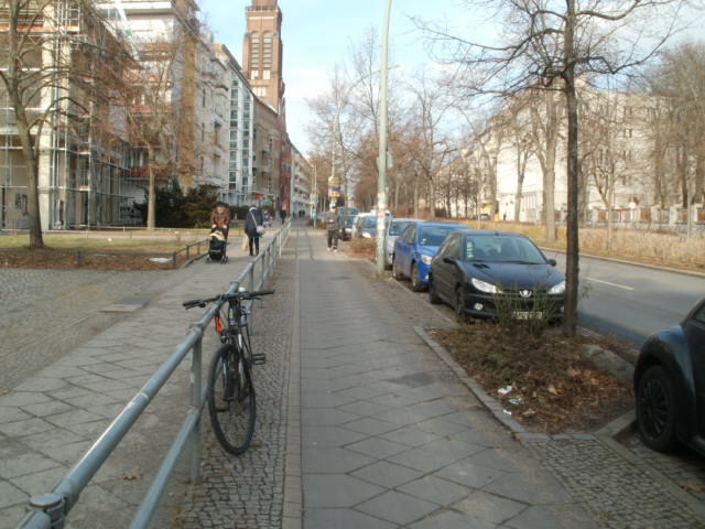 Bike lane in Berlin - separated from foot traffic by a fence and motor traffic by trees and parked cars.  Yes, there is a pedestrian walking there...