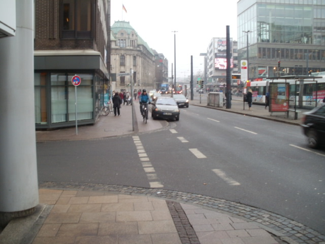 Car in the bike lane in Bremen.  Sigh.  An annoyed cyclist riding by.
