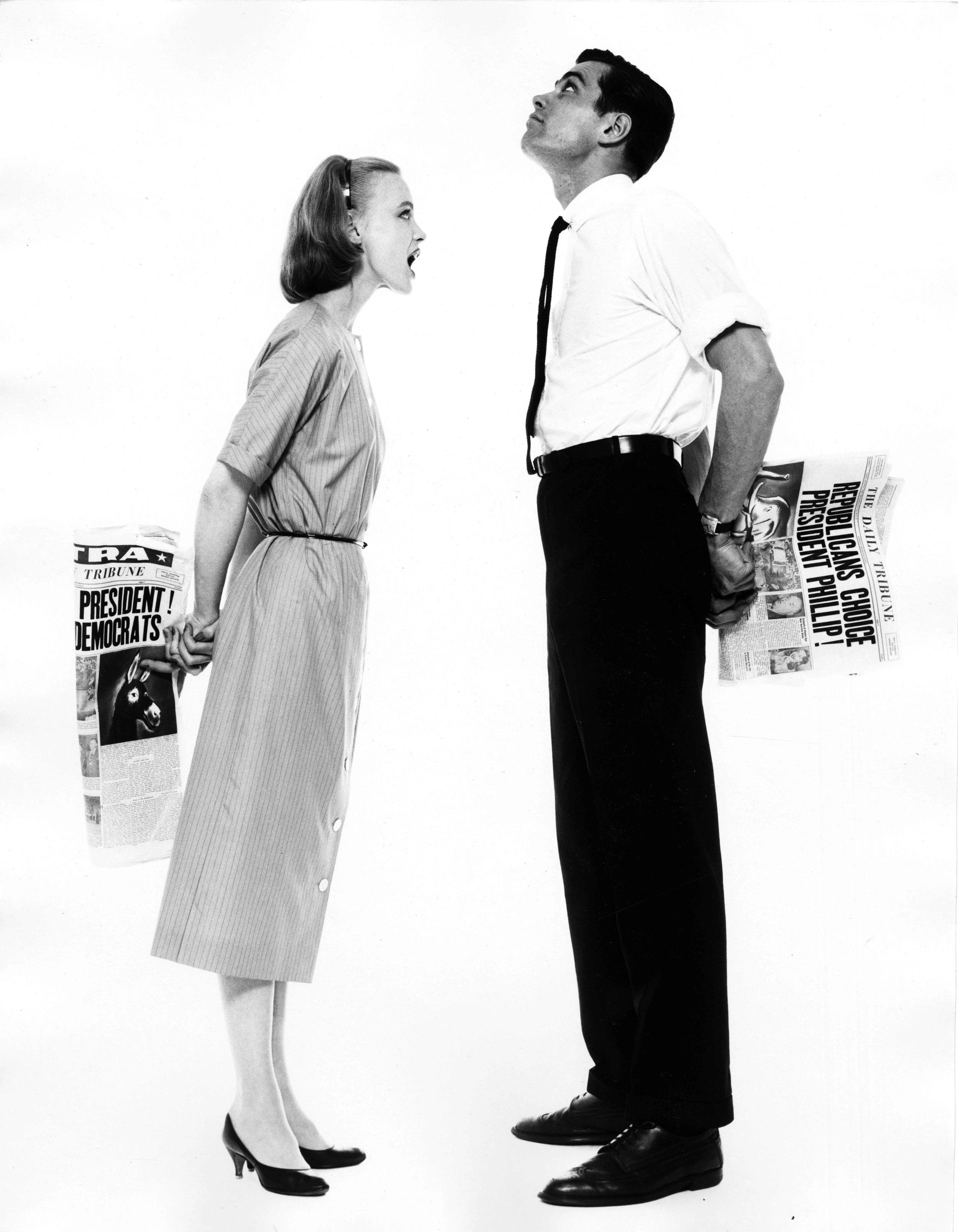 16_25_Woman and man holding newspaper behind their backs_Dan Wynn Archive.jpeg