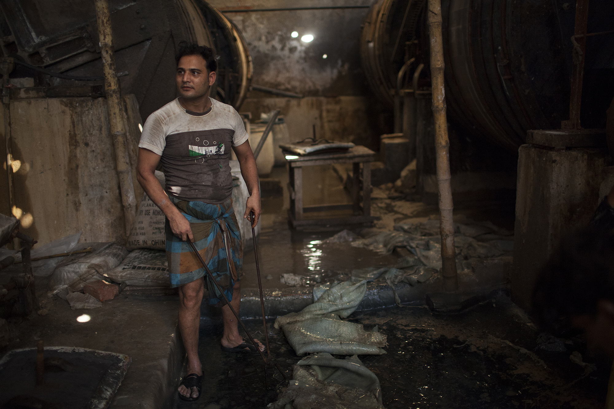 Shofiko Islam, 40, helps place cattle hides into a metal drum where the hides are treated with over 100 chemicals in a tannery in the Hazaribagh district of Dhaka, Bangladesh. (Credit: Will Baxter)