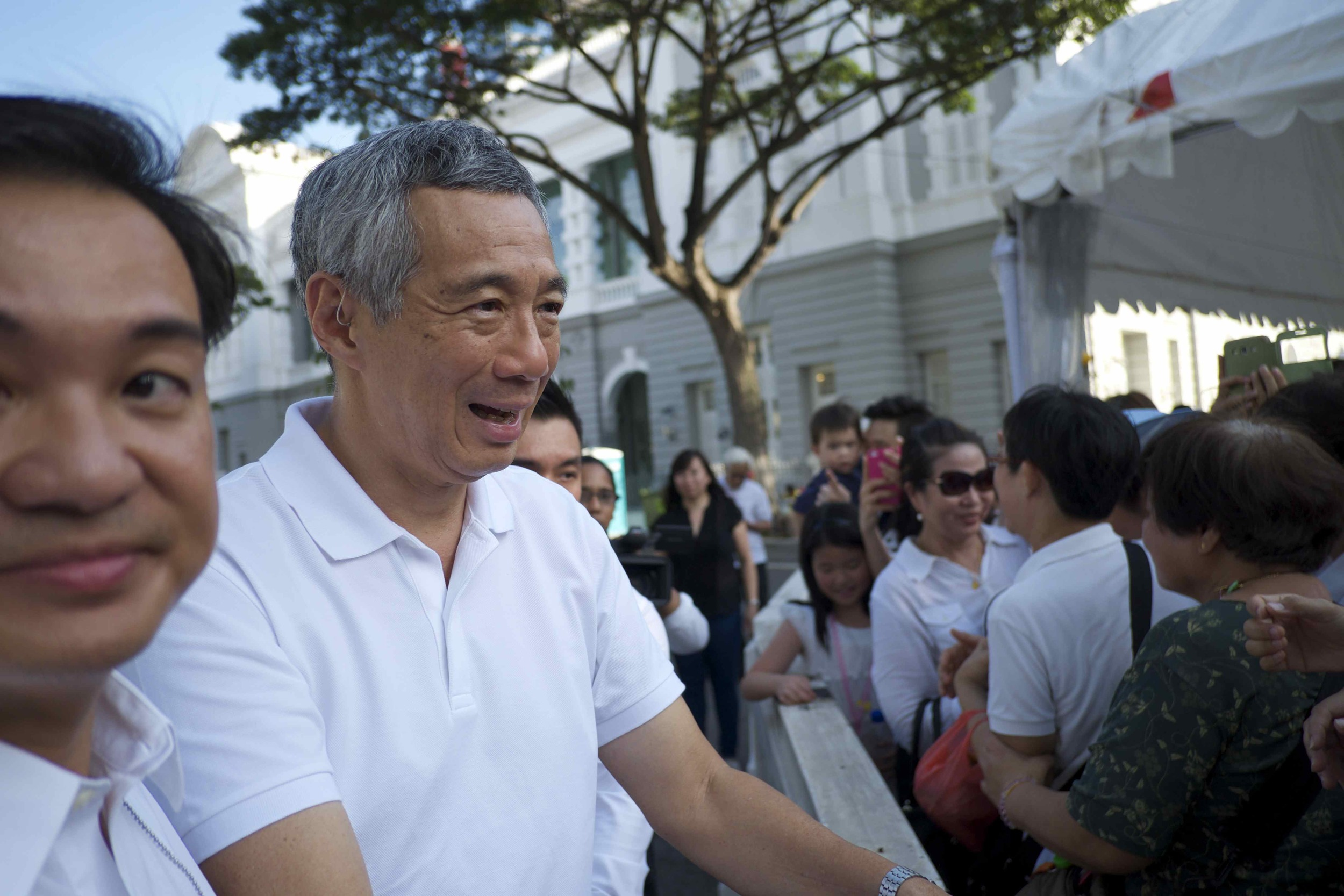 Lee Hsien Loong, current Singapore prime minister and Lee Kuan Yew's son, greet mourners waiting outside the Parliament House to pay their respects to the former PM. (Credit: Dene-Hern Chen)