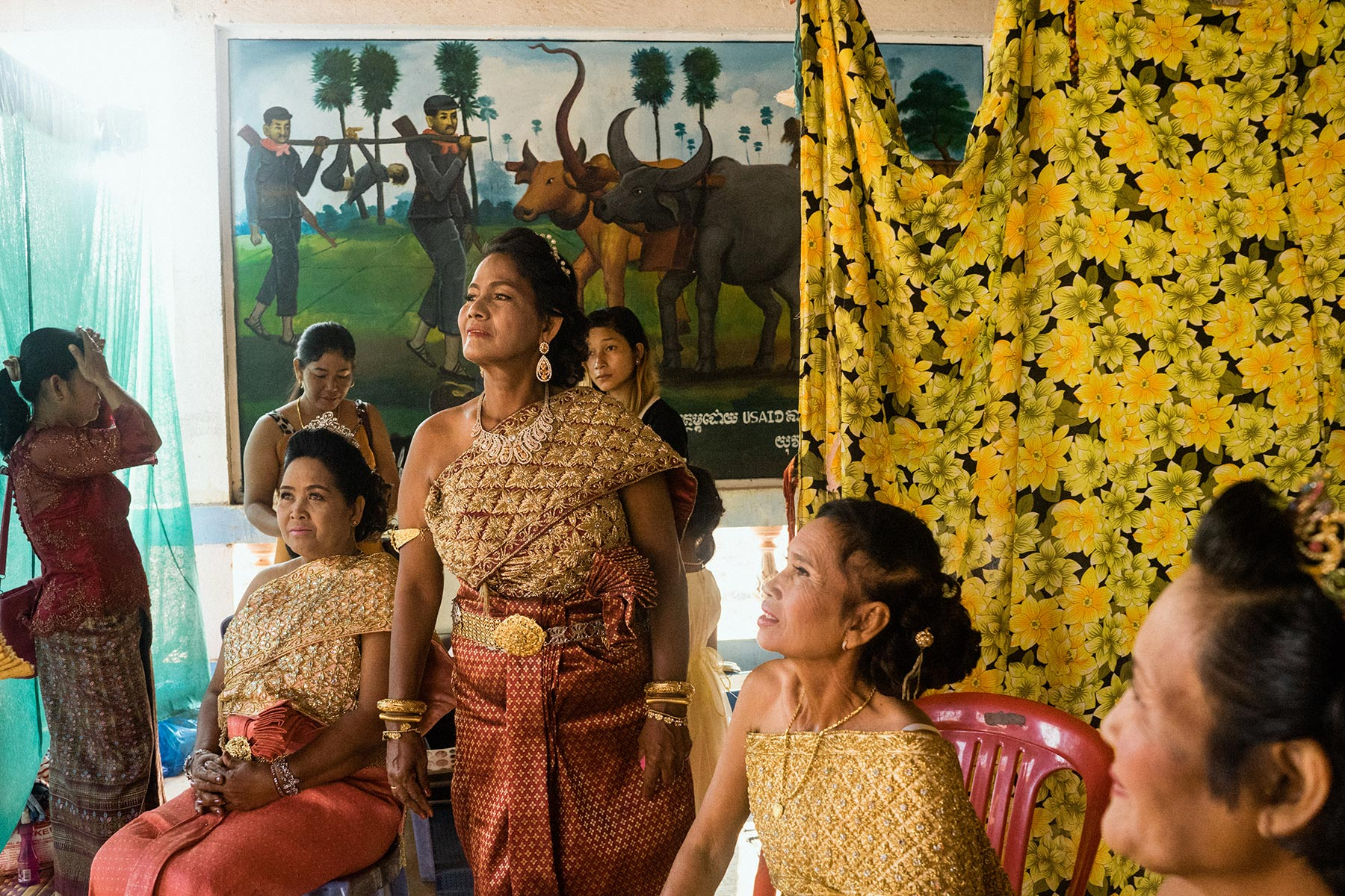 As they get ready for the remarriage ceremony, some of the brides sit in front of a mural illustrating war crimes carried out by the Khmer Rouge.