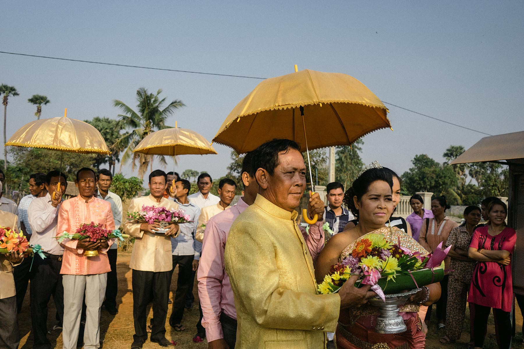 Yim Ran (right) and Sok Hort join in the fruit parade that traditionally accompanies a Cambodian wedding.