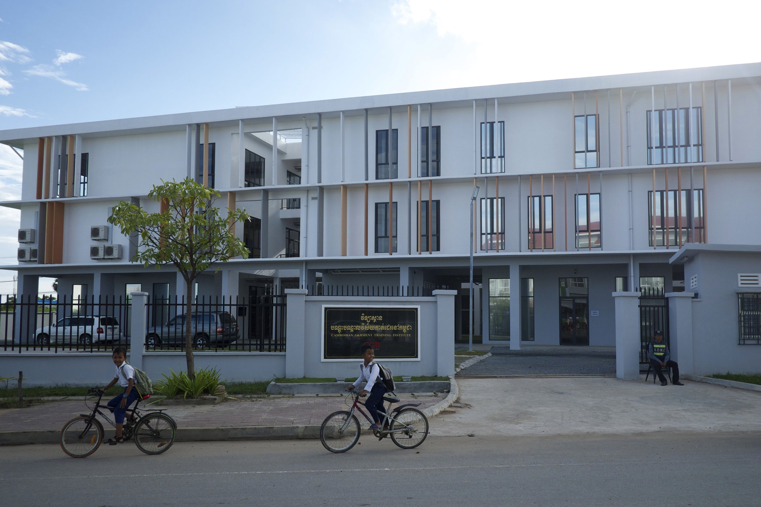 Children cycle past a newly opened vocational training institute for Cambodian garment workers in Phnom Penh. (Credit: Dene-Hern Chen)
