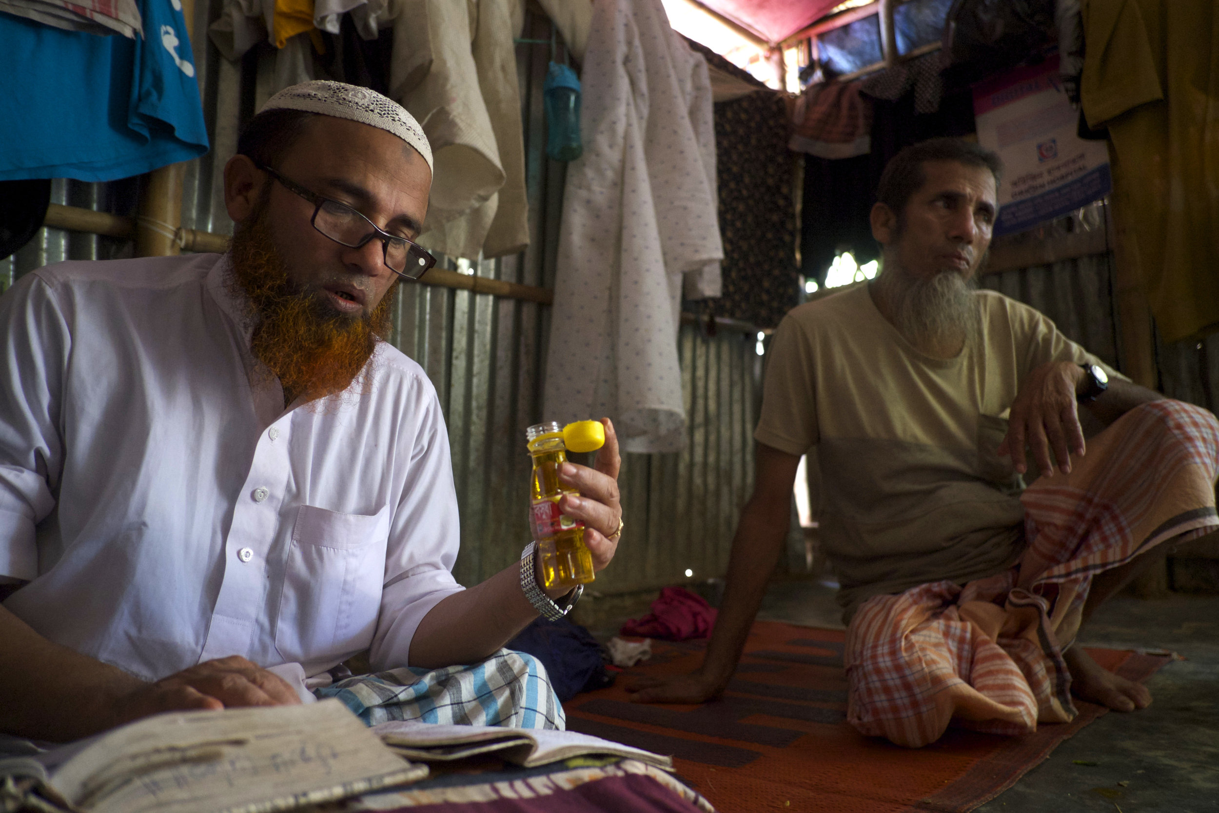 Gias Uddin, a religious teacher, recites verses from the Quran for Abdul Amin, right, who says that he has been in pain since he fled Myanmar in 2017. (Creid