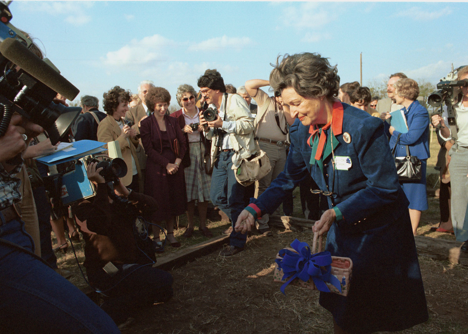 Lady Bird Johnson spreads seeds on the site of the National Wildflower Research Center.LBJ Library photo by Frank Wolfe.