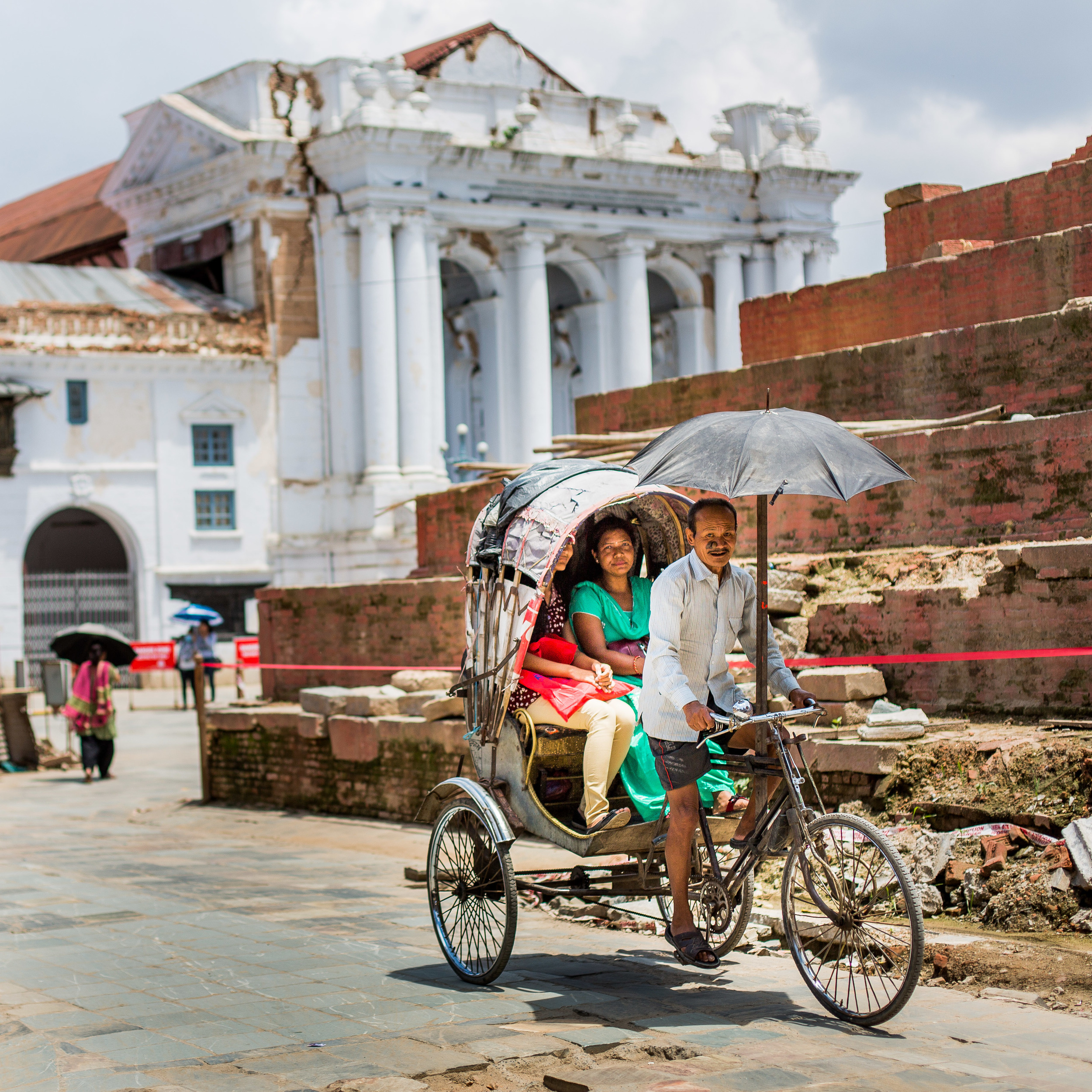 Life continues and rickshaw drivers again cycle past the destroyed Gaddi Baithak in Basantapur Durbar Square. This European style building was built as a part of the palace in the early twentieth century.